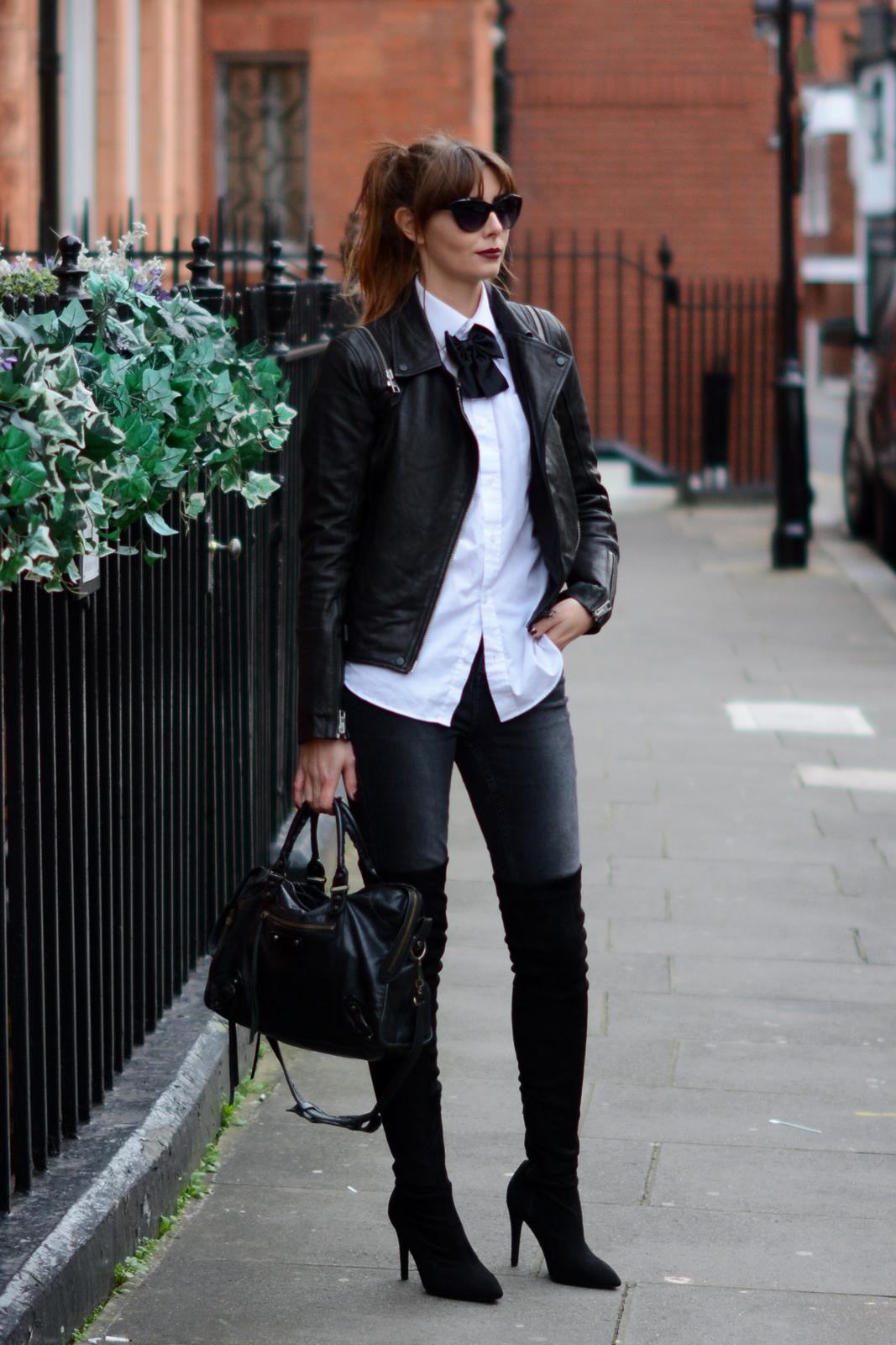 EJSTYLE - Black acid wash skinny jeans, Next heeled OTK thigh high boots, Balenciaga bag, all saints leather biker jacket, white shirt, black bowtie, Saint Laurent Street style, London