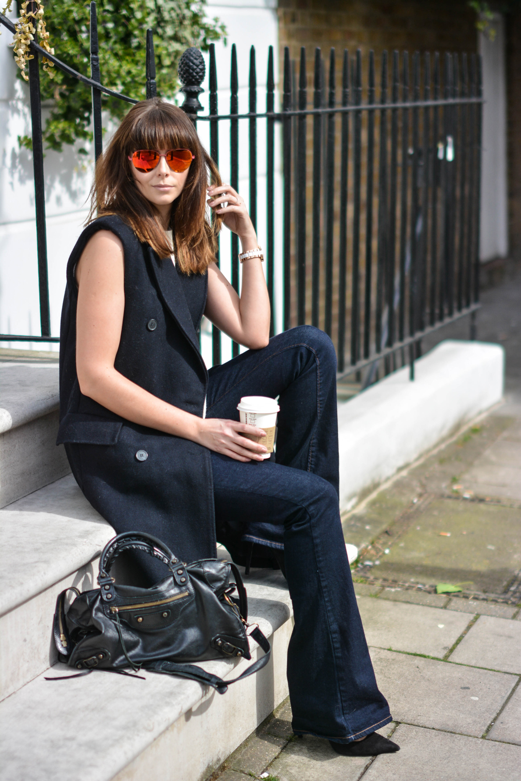 EJSTYLE - Emma Hill, H&M Studio sleeveless coat, flare jeans, Kurt Geiger aviator sunglasses, Balenciaga le city bag, Pointed black suede court shoes heels