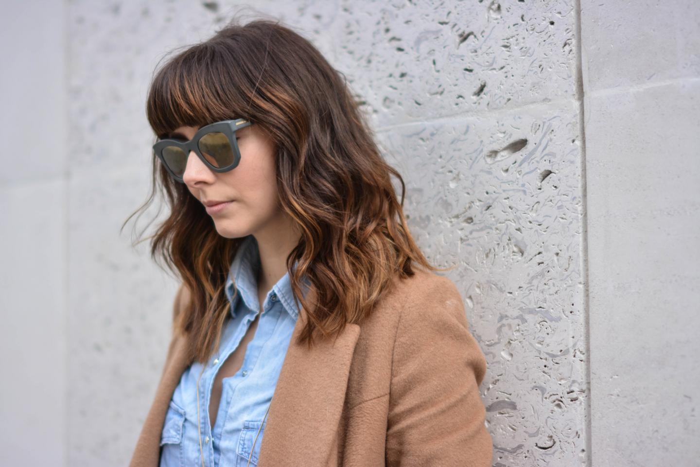 EJSTYLE - Emma Hill, Stella McCartney Sunglasses, choppy long bob hair with bangs fringe, denim shirt, camel coat