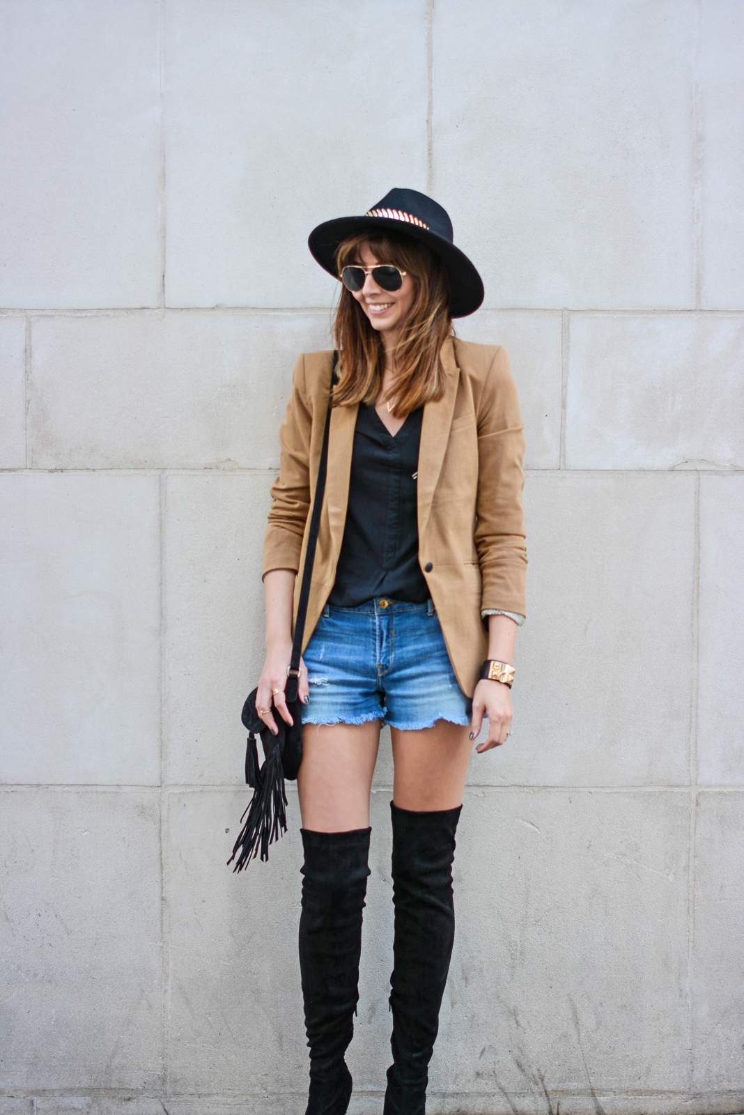 EJSTYLE - Emma Hill wearing Camel blazer, black shirt, black suede thigh high OTK boots, Fedora hat, denim shorts, black suede fringe tassel bag, collier de chien cuff bracelet, aviator sunglasses