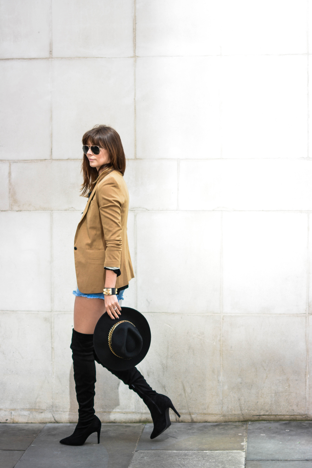 EJSTYLE - Emma Hill wearing Camel blazer, black suede thigh high OTK boots, Fedora hat, denim shorts, aviator sunglasses