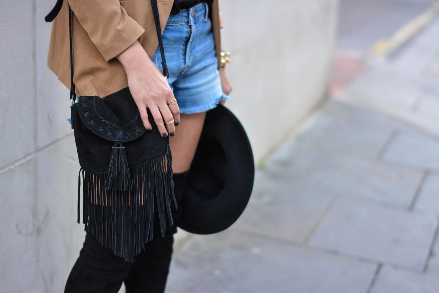 EJSTYLE - Emma Hill wearing Camel blazer, black suede thigh high OTK boots, Fedora hat, denim shorts, black suede fringe bag, gold rings