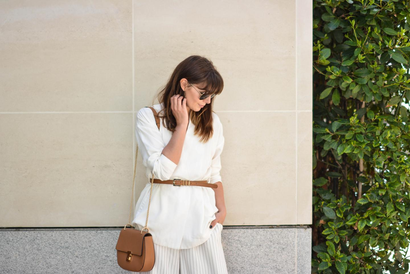EJSTYLE - Emma Hill wearing Gestuz white wrap jacket, tan skinny waist belt, gold handcuff necklace, Finders Keepers white pinstripe culottes, gold aviator sunglasses