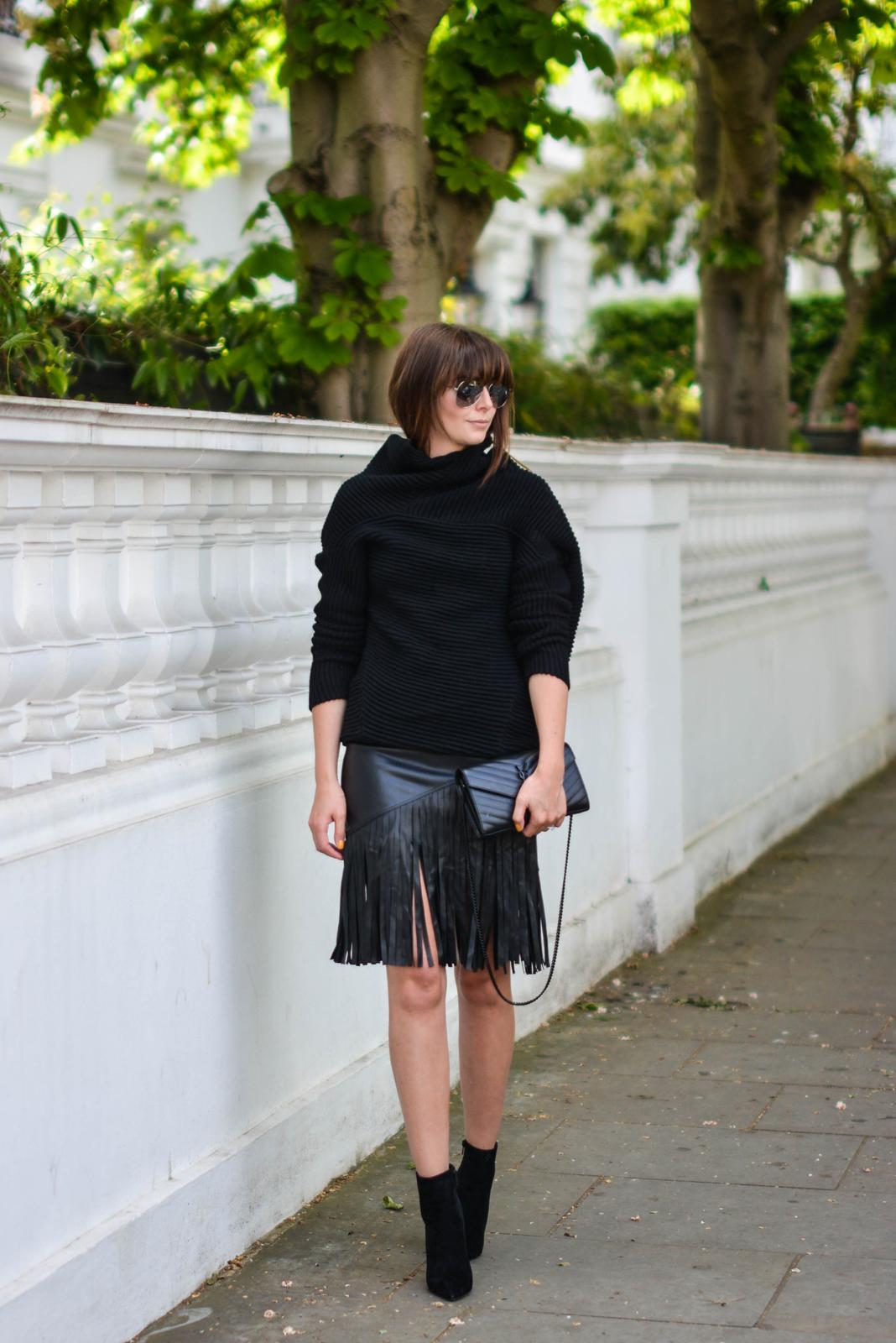 EJSTYLE - Emma Hill wears River Island faux leather fringe tassel skirt, Romwe black jumper, heeled ankle boots, YSL quilted envelope clutch bag, all black OOTD