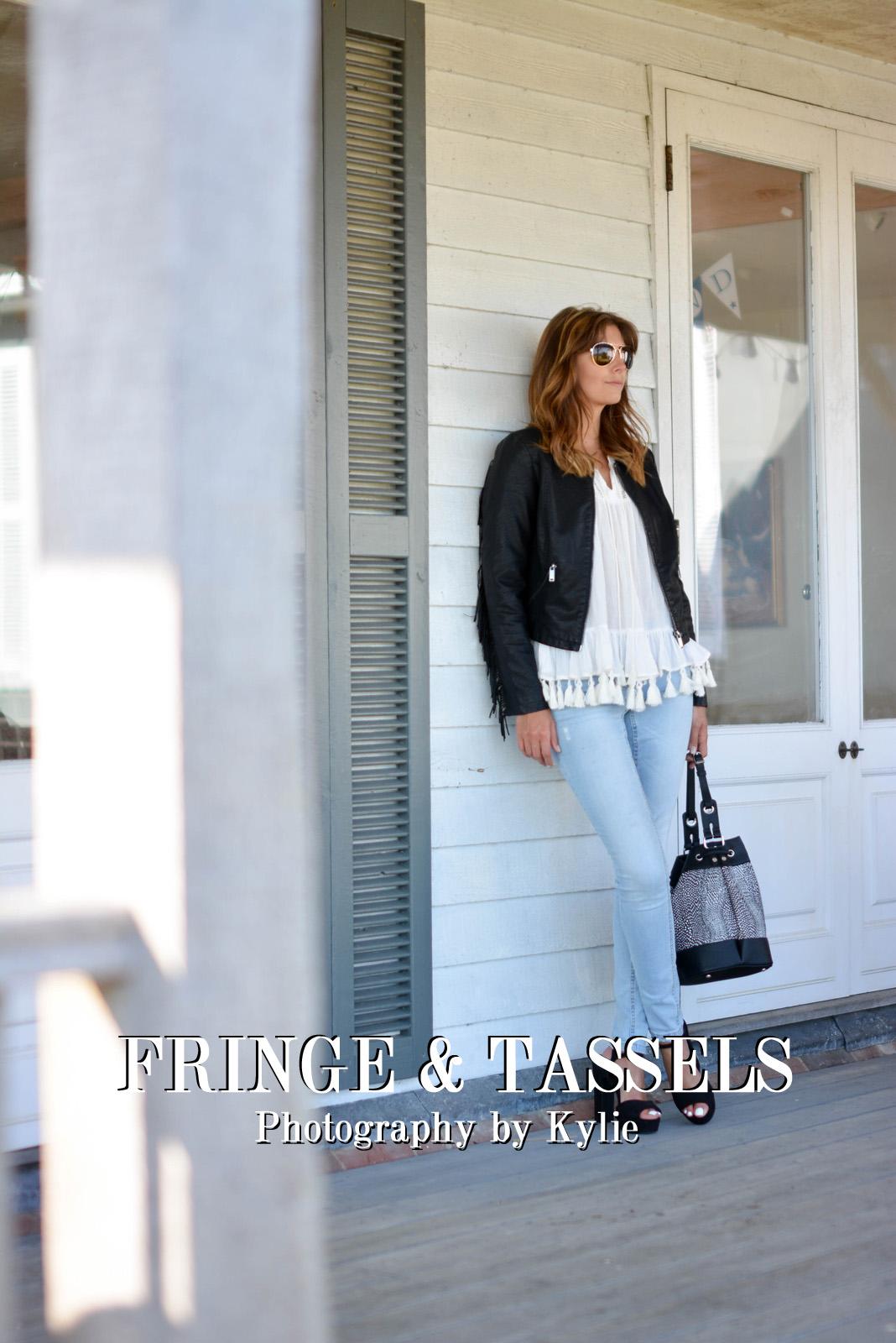 EJSTYLE - Emma Hill wears black tassel fringe leather jacket, tassel trim tunic top, bleach wash skinny jeans, black suede platform sandals, black grey snake bucket bag, aviator sunglasses, OOTD, title