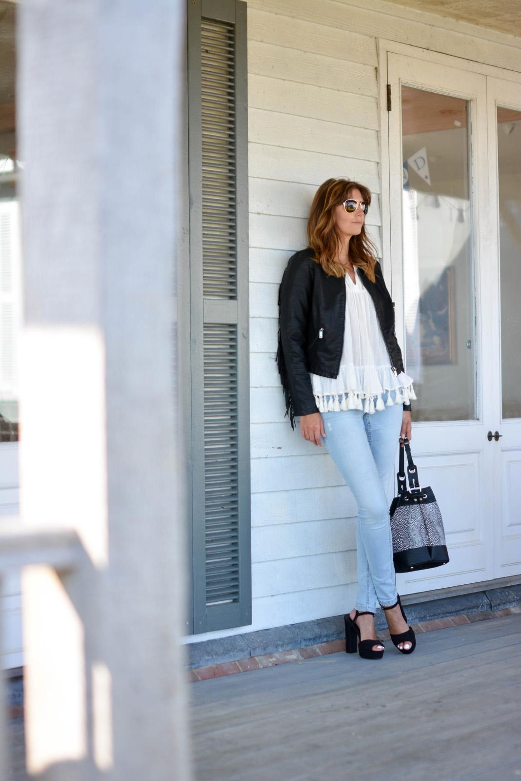 EJSTYLE - Emma Hill wears black tassel fringe leather jacket, tassel trim tunic top, bleach wash skinny jeans, black suede platform sandals, black grey snake bucket bag, aviator sunglasses, OOTD