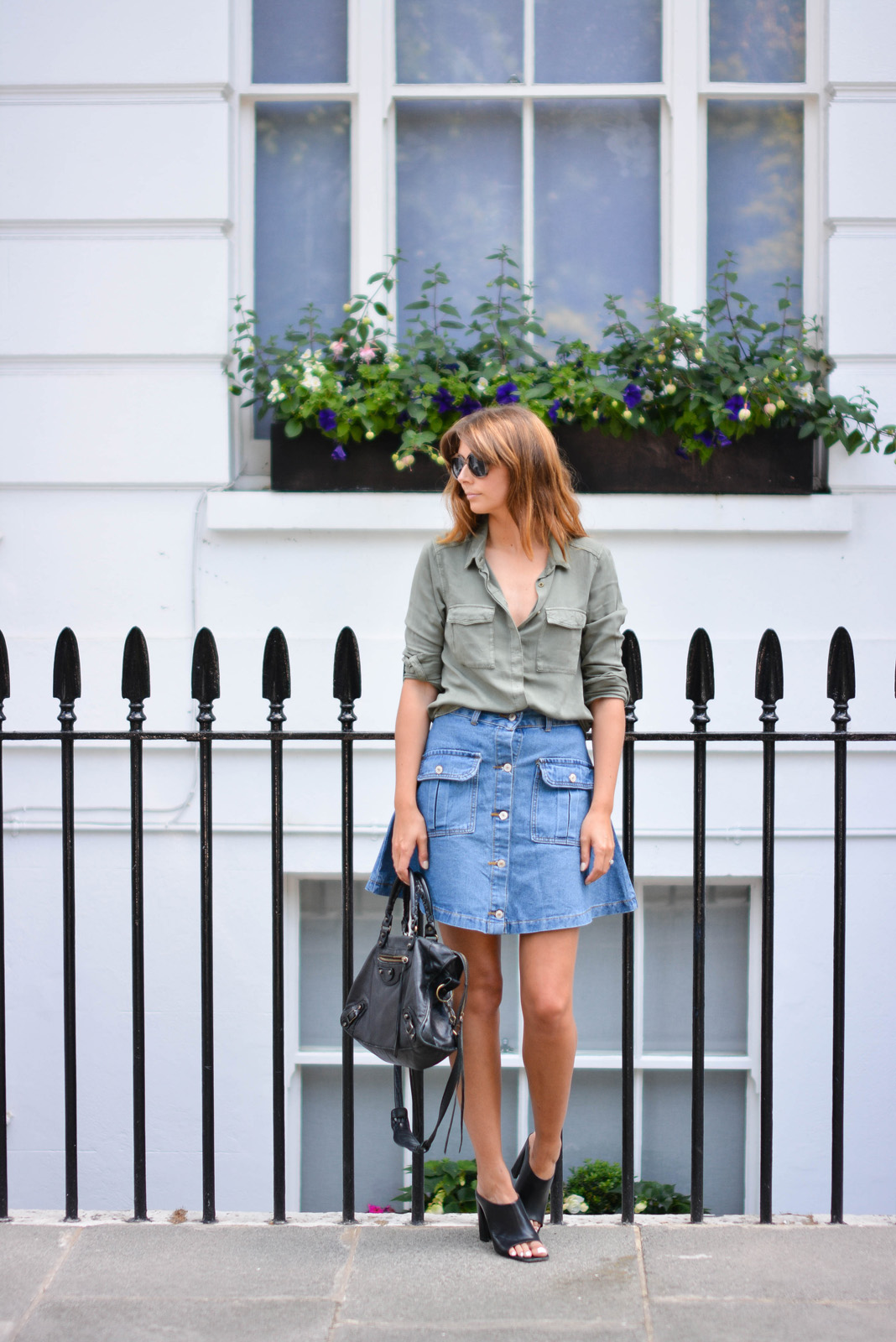 EJSTYLE - Emma Hill wears button up denim skirt with pockets with a khaki shirt, Balenciaga bag, black leather mules, heels, how to dress for summer