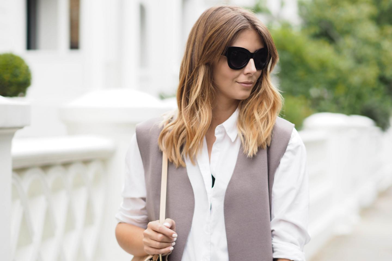 EJSTYLE - Emma Hill wears black cat eye sunglasses, taupe sleeveless coat, white shirt, balayage long bob, LOB hairstyle