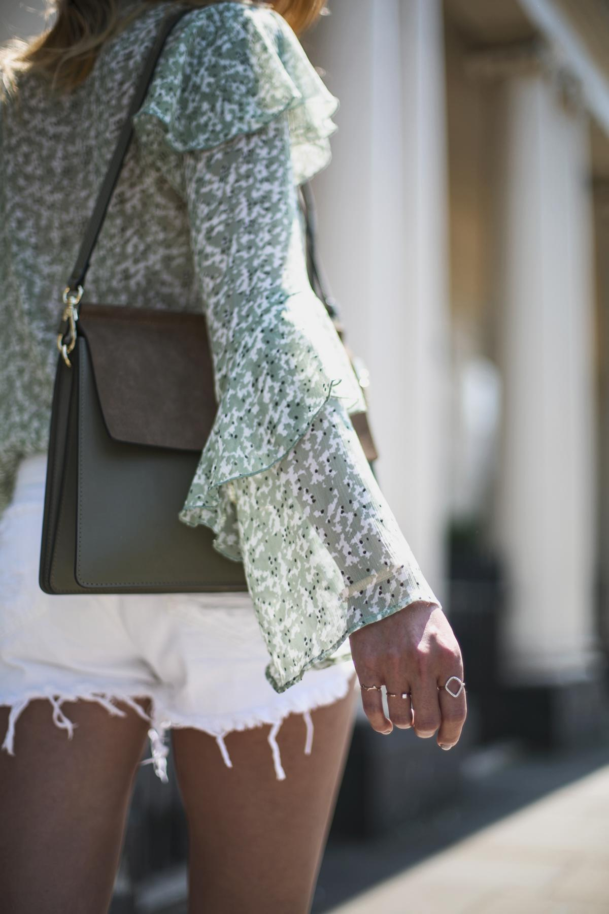 Gren floaty top with flare sleeves, white ripped denim shorts, khaki chloe faye bag, rings