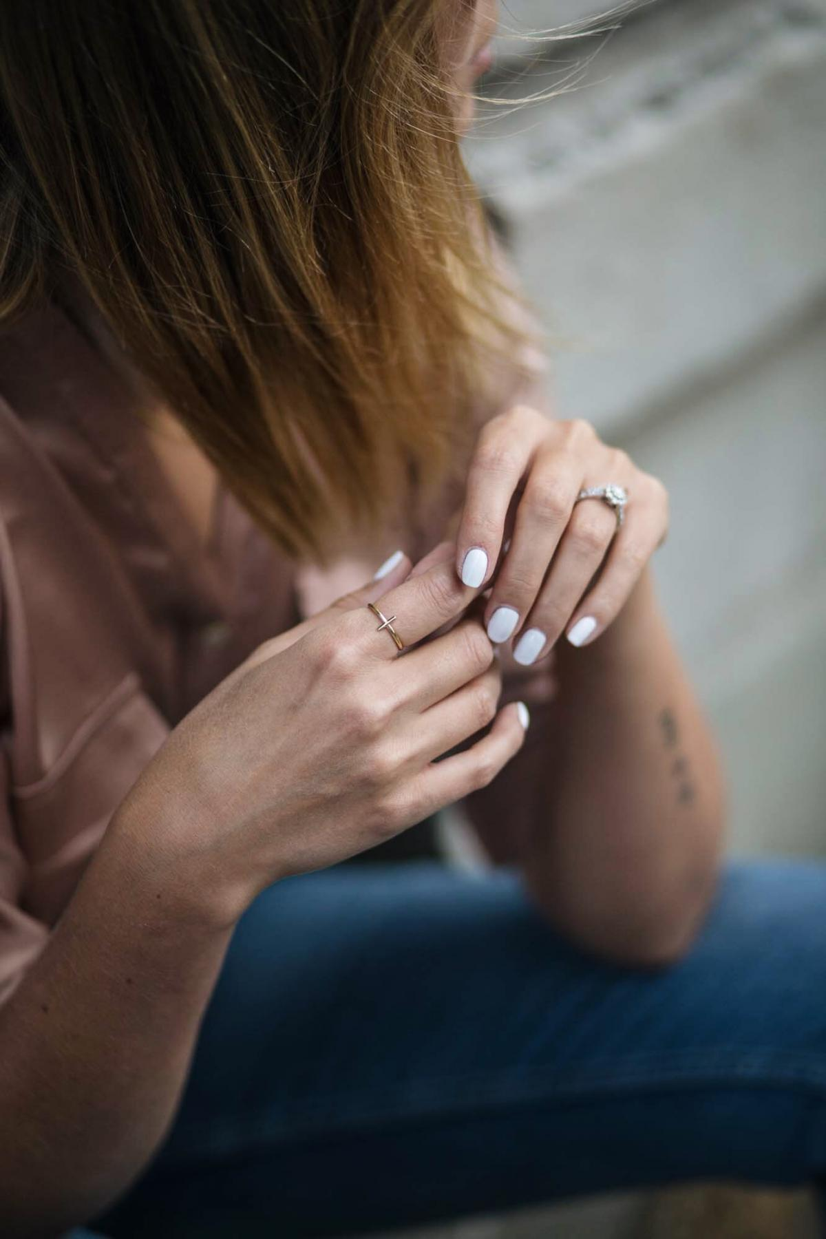 satin shirt, gold cross ring, white nails manicure
