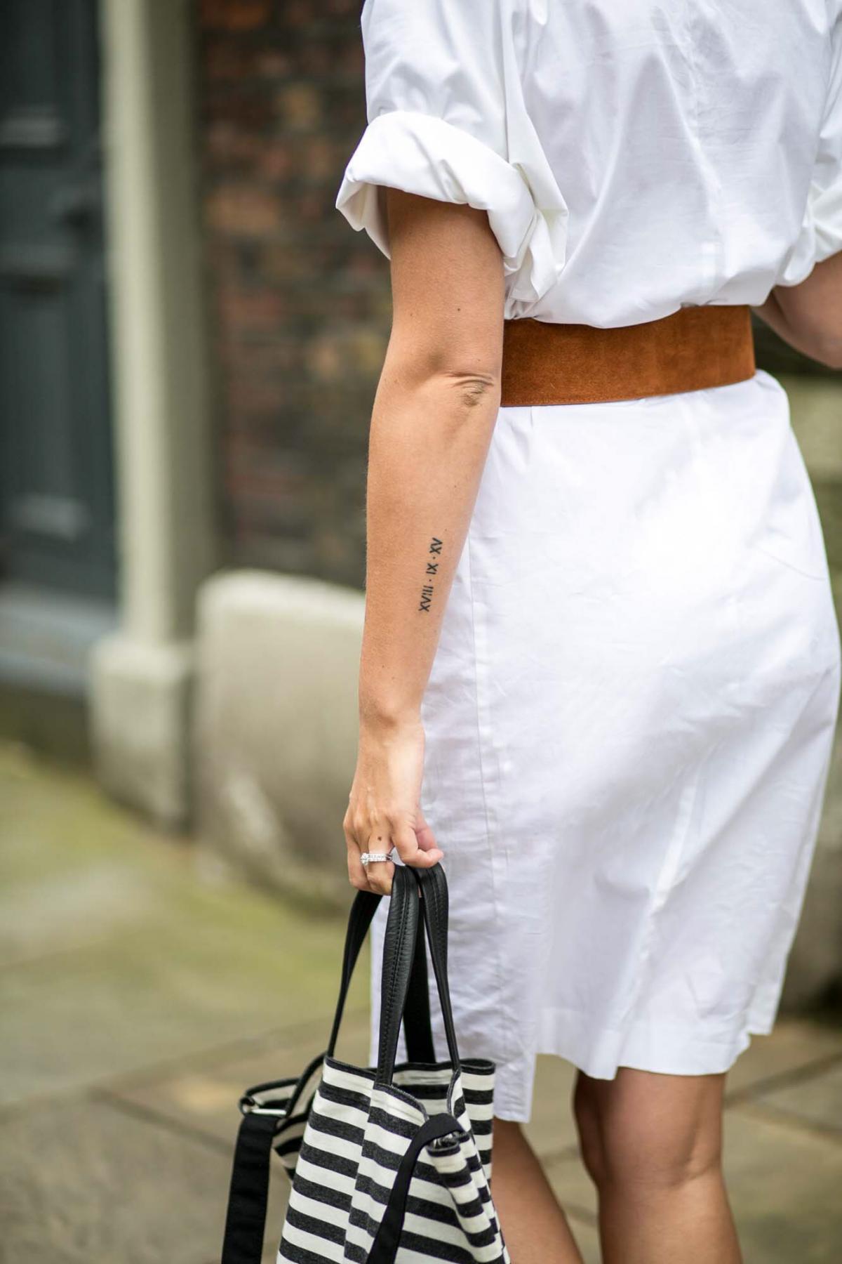 white shirt dress, tan suede waist belt, roman numerals wedding date arm tattoo