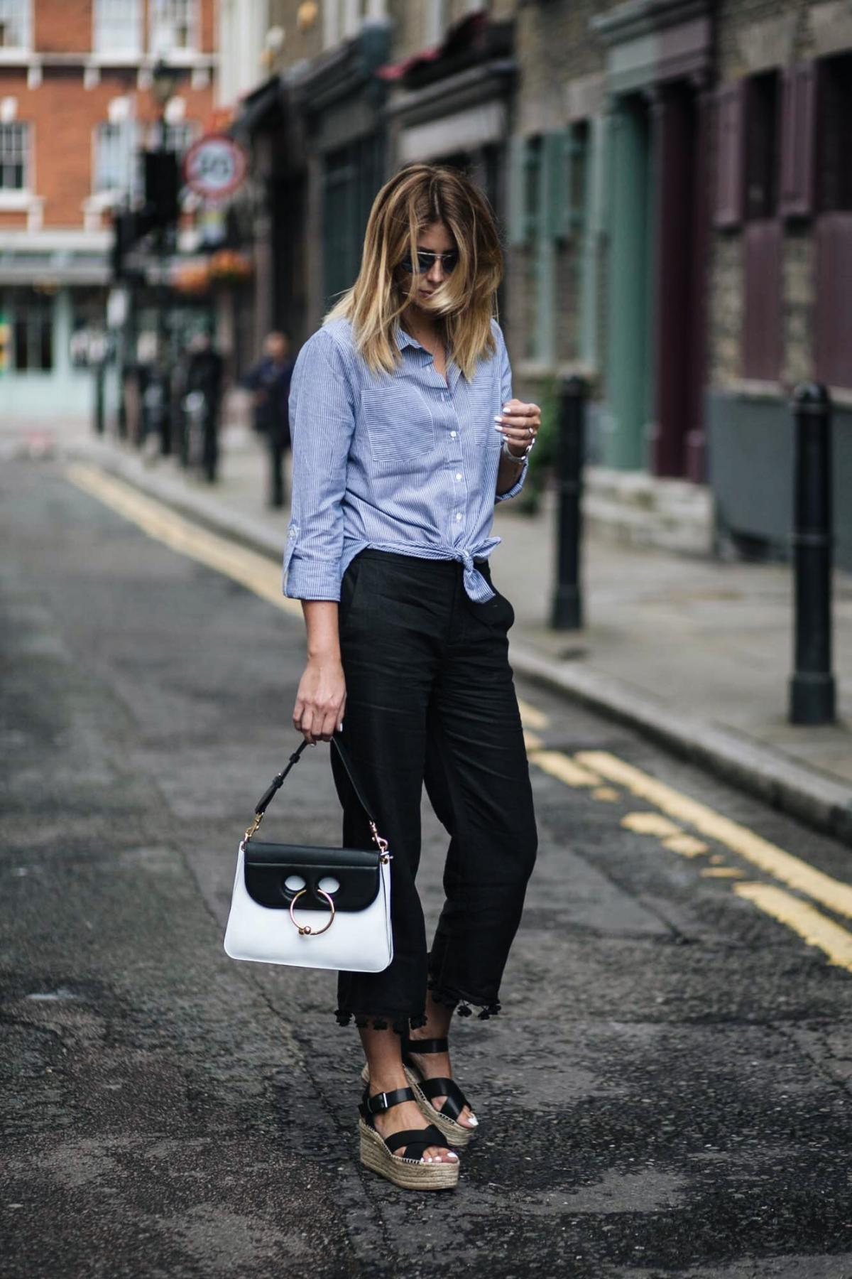 Zara pom pom hem black cropped trousers, wedge espadrilles, street style, JW Anderson monochrome Piercing bag, blue pinstripe shirt tied in a knot, chic summer outfit