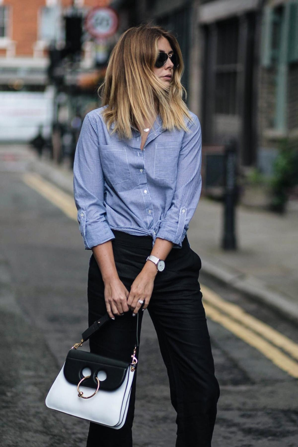 blue pinstripe shirt tied in a knot at the waist, black trousers, london street style