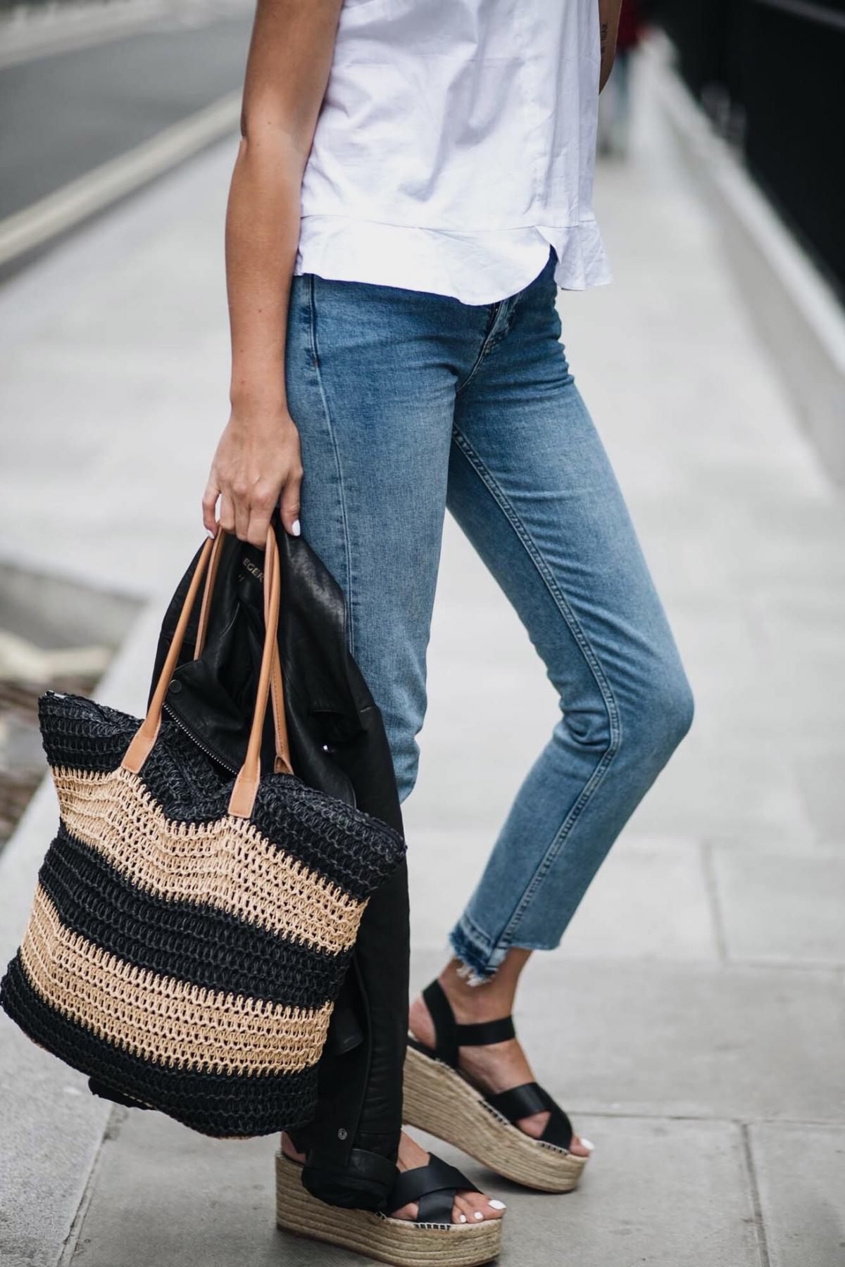 white frill hem sleeveless top, straight leg jeans with stepped hem, biker jacket, straw woven beach bag, wedge platform espadrilles sandals