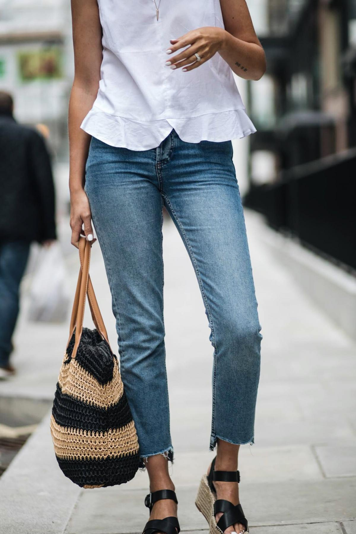 straw shopper bag, straight leg jeans, frill hem sleeveless white top, white nails manicure