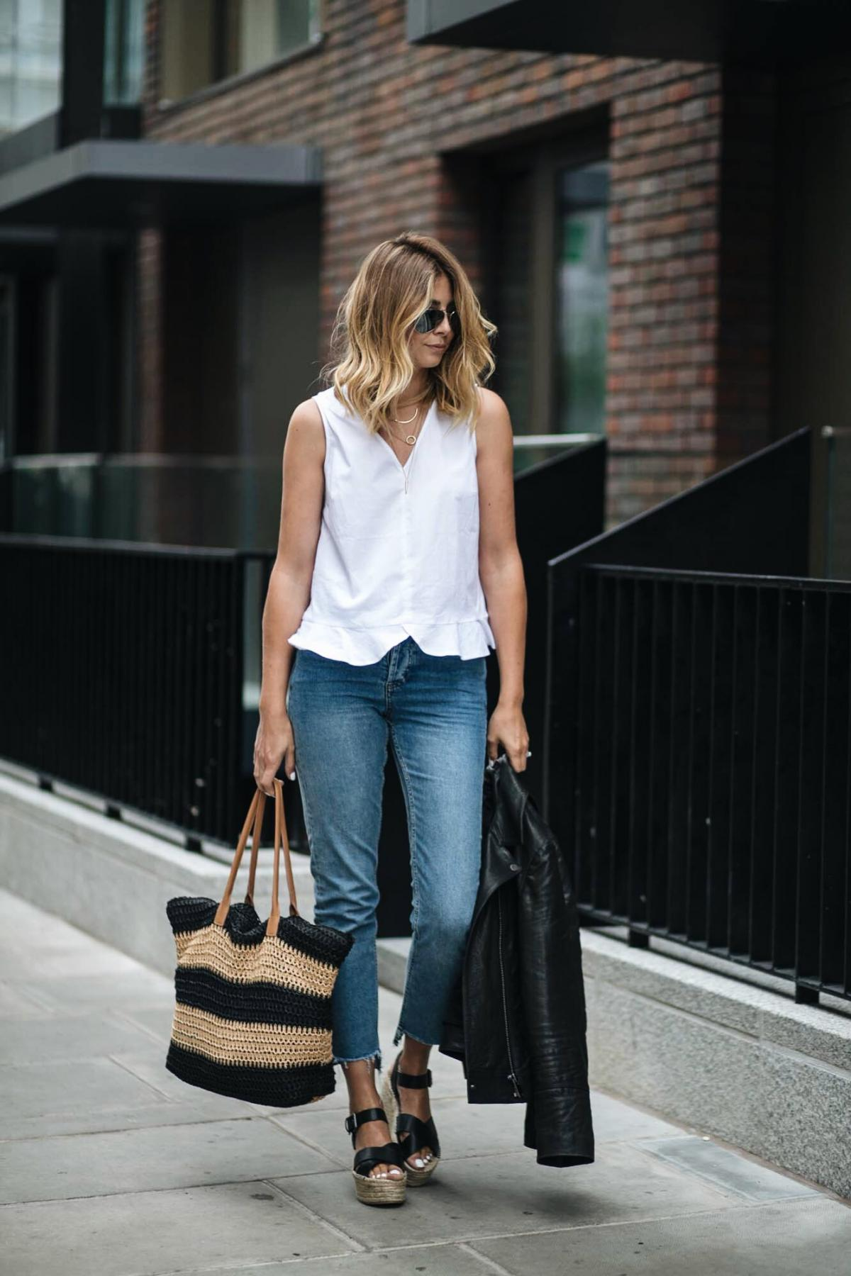 white frill hem sleeveless top, straight leg jeans with stepped hem, biker jacket, straw woven beach bag, wedge platform espadrilles sandals, summer outfit