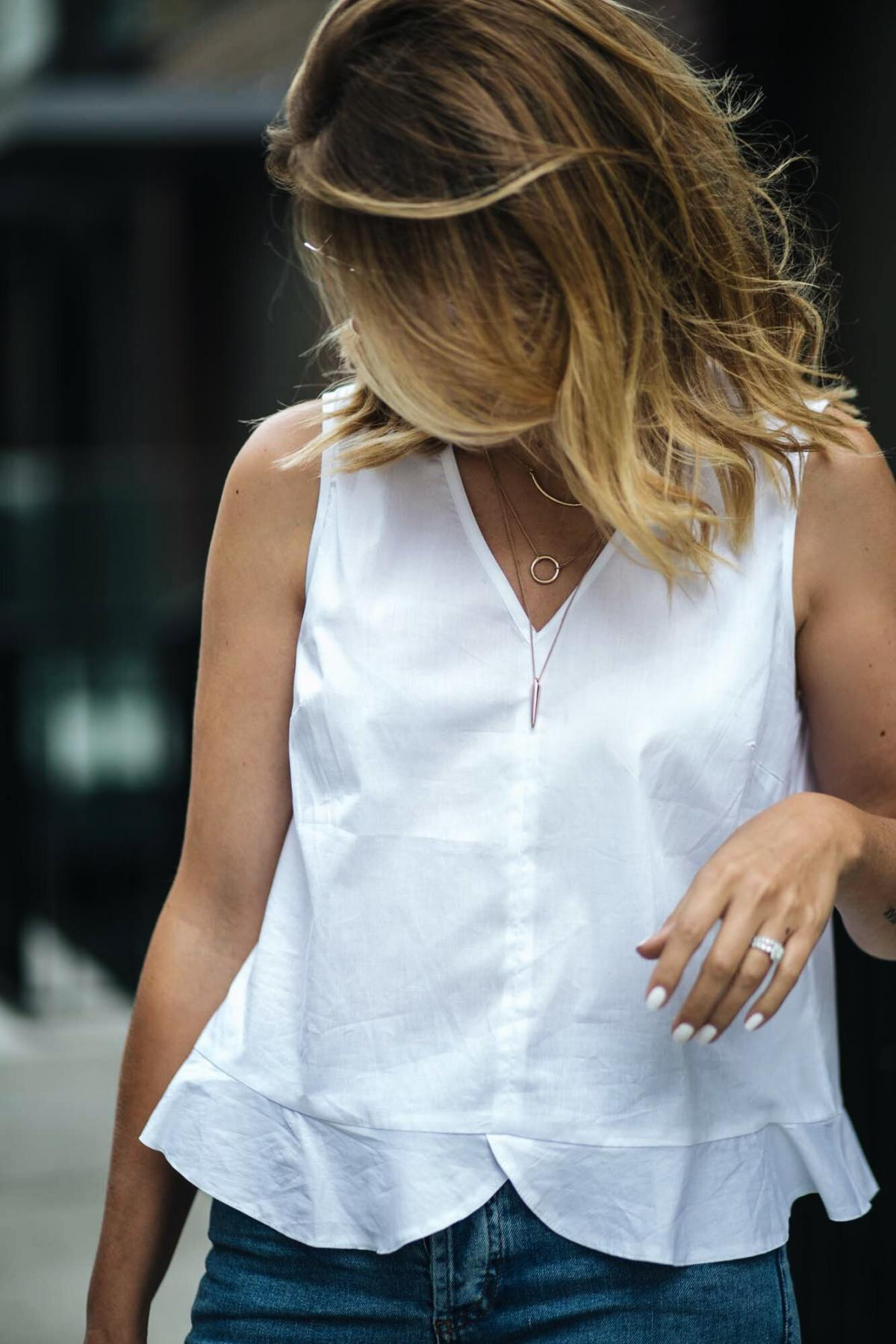 gold layered necklaces, white frill hem sleeveless top, white nails manicure