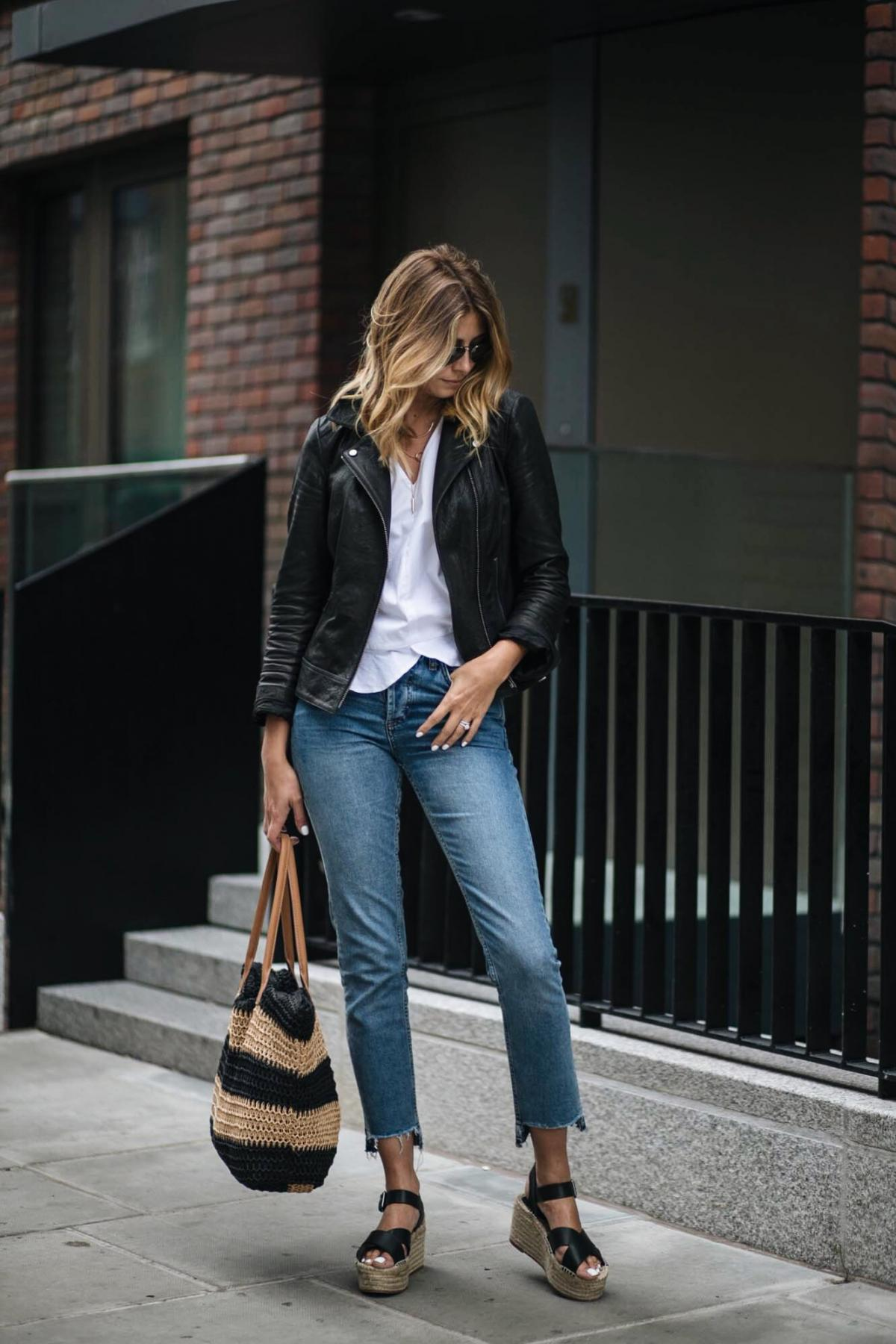 black leather biker jacket, white top, stepped hem straight leg jeans, straw shopper bag, wedge espadrilles, summer street style, outfit