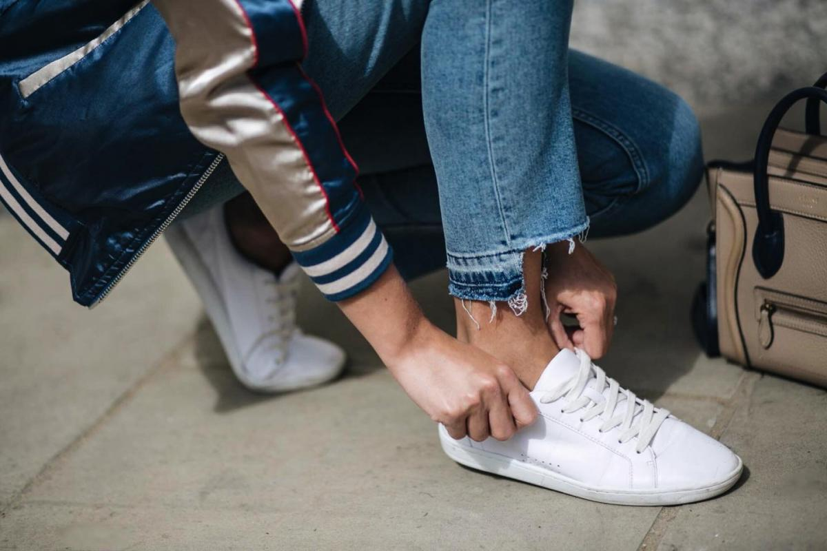 white lace up trainers, satin bomber jacket, stepped hem jeans, street style