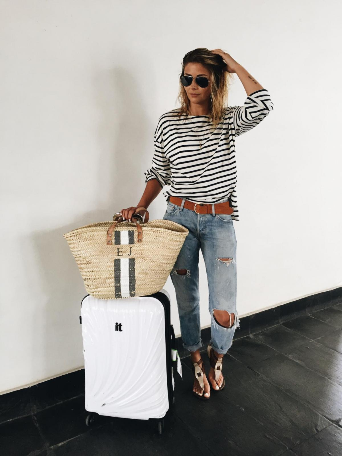travel airport outfit, breton stripe t shirt, straw tote bag, ripped boyfriend jeans, tan belt, white suitcase, tan sandals, straw hat,