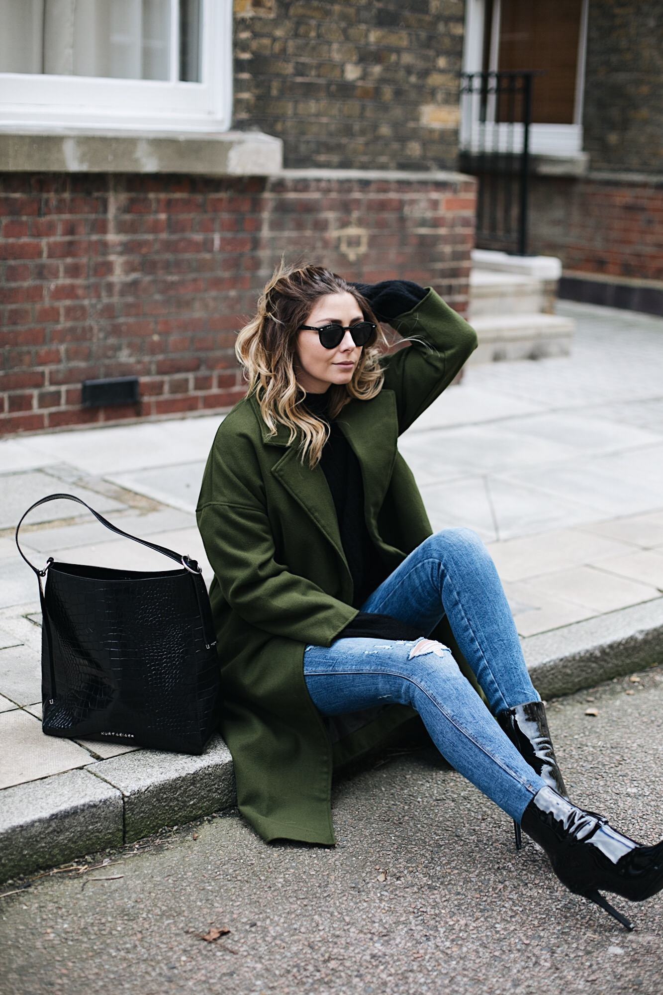 Emma Hill wears khaki coat, black sweater, ripped skinny jeans, large croc bag, black patent vinyl heeled ankle boots, round Rayban sunglasses, chic winter outfit