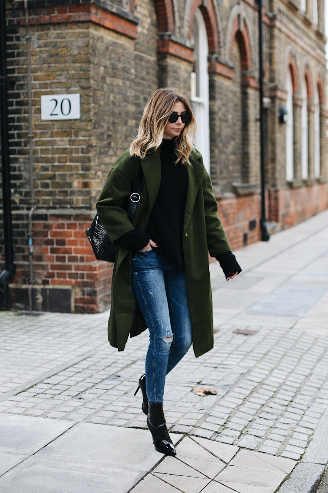 khaki coat, black sweater, ripped skinny jeans, black vinyl patent heeled ankle boots, large black croc bag, chic winter outfit