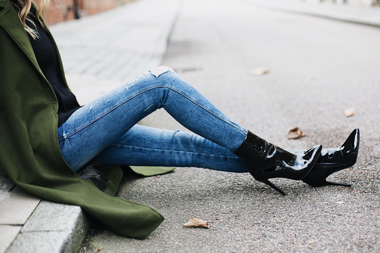 ripped skinny jeans, black patent vinyl heeled ankle boots, khaki coat