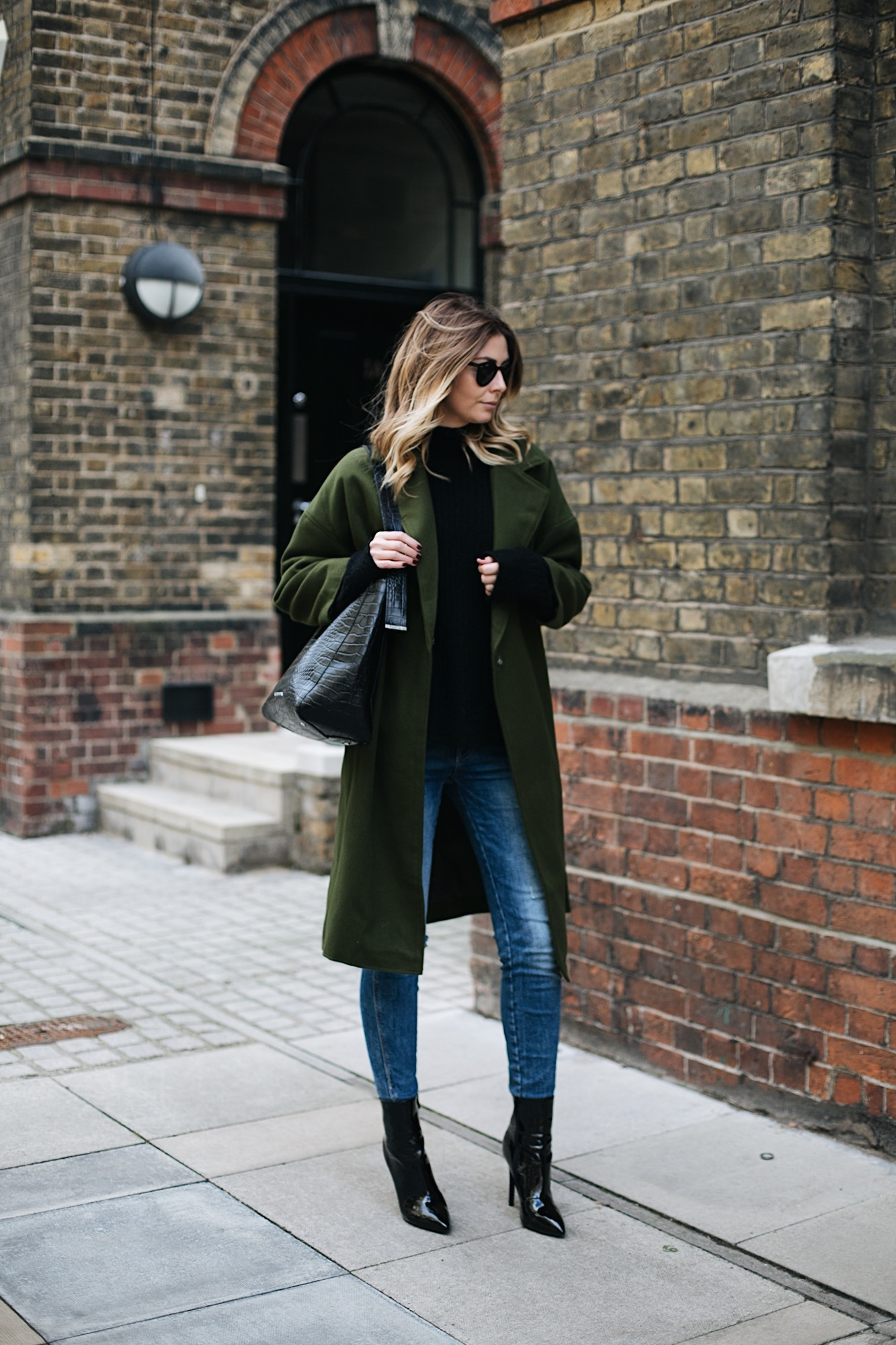 Emma Hill wears khaki coat, black sweater, ripped skinny jeans, black vinyl patent heeled ankle boots, large black croc bag, chic winter outfit