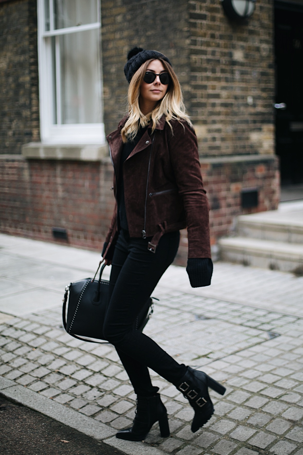 Emma Hill wears brown suede jacket, black skinny jeans, black sweater, knitted bobble hat, buckled heeled ankle boots, studded Givenchy Antigona bag, Round Rayban sunglasses, winter outfit ideas