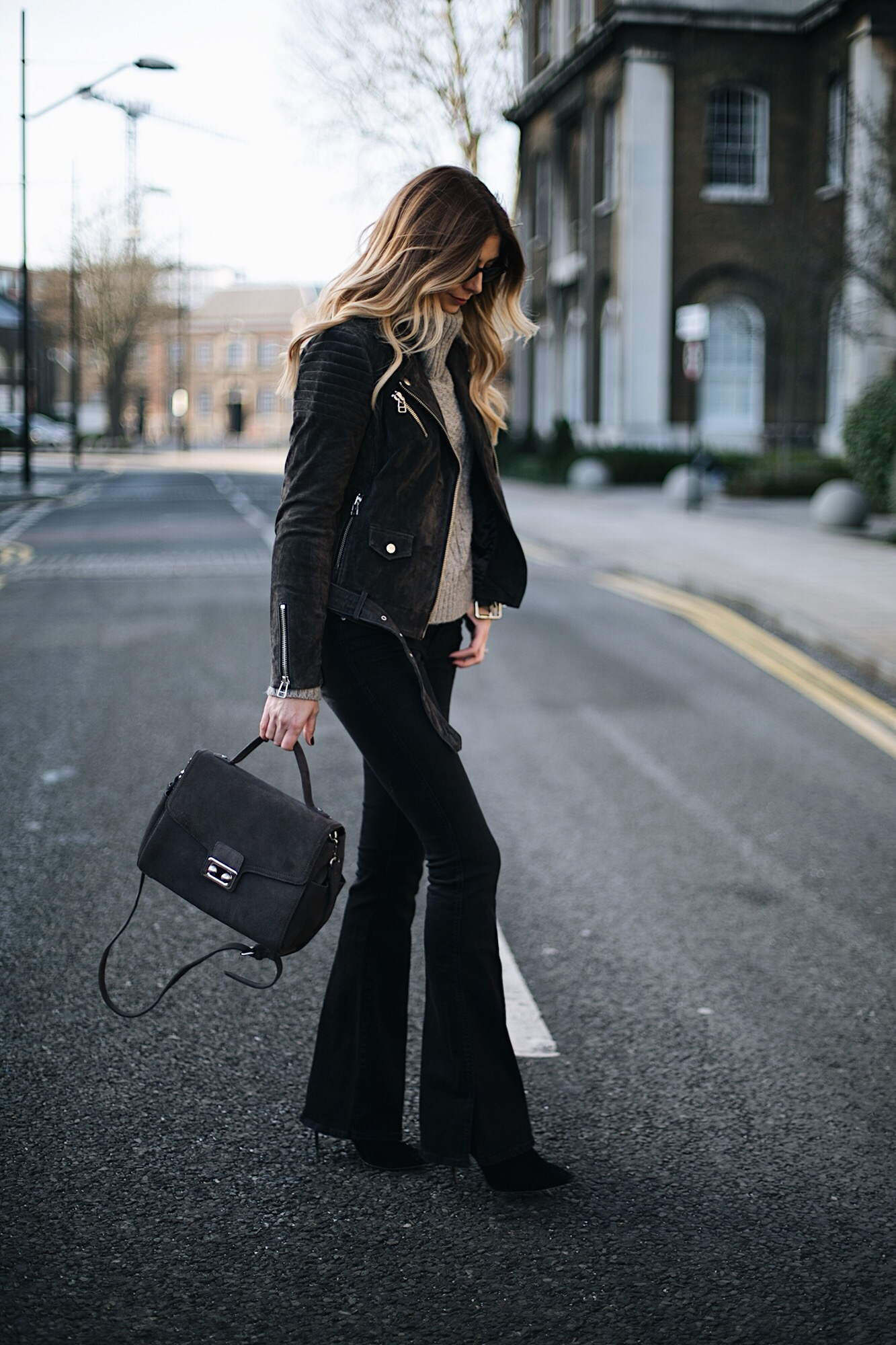 Emma Hill wears black flare jeans, grey suede biker jacket, grey roll neck sweater grey suede bag, chic winter outfit