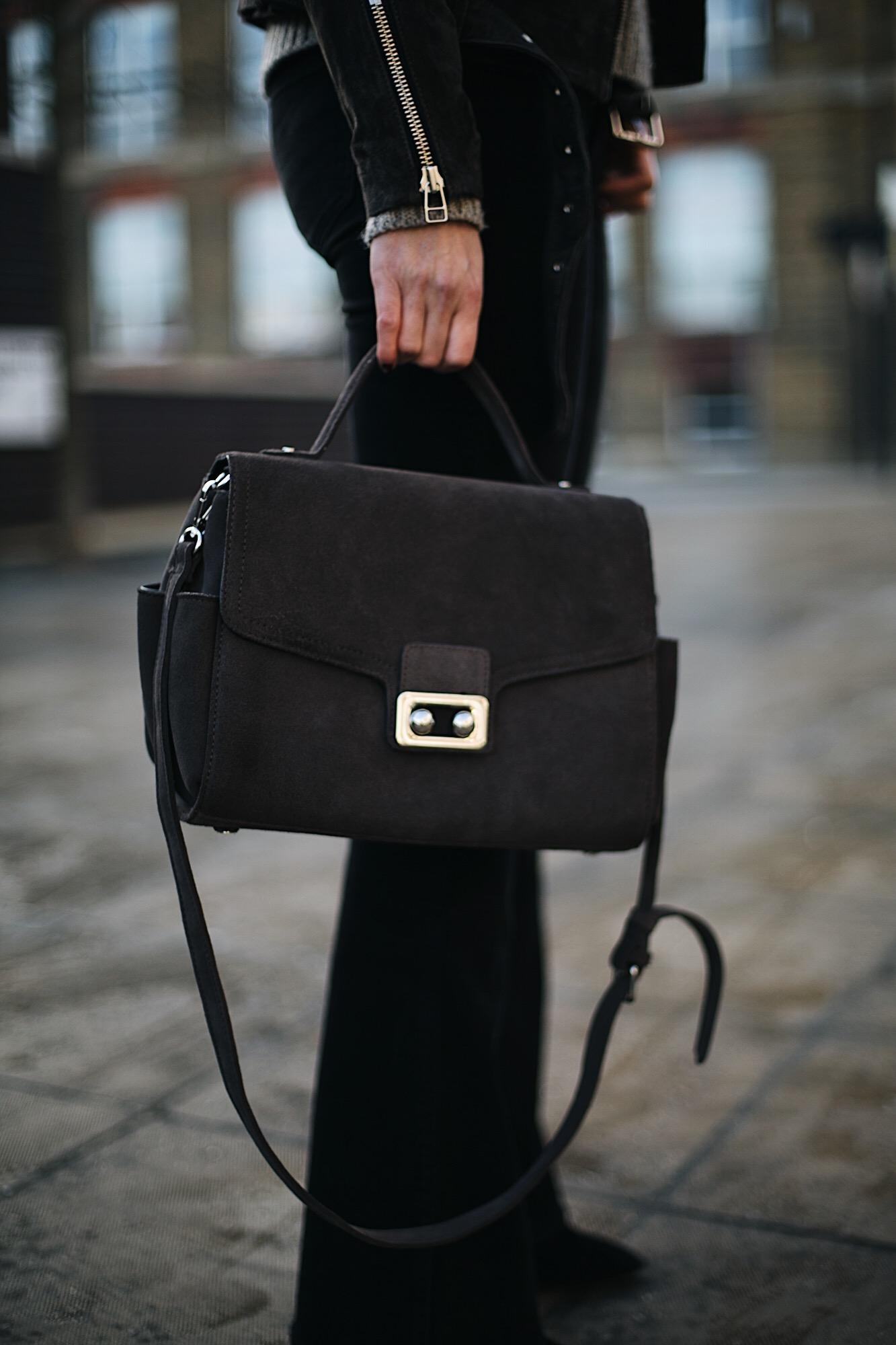 black flare jeans, grey suede bag
