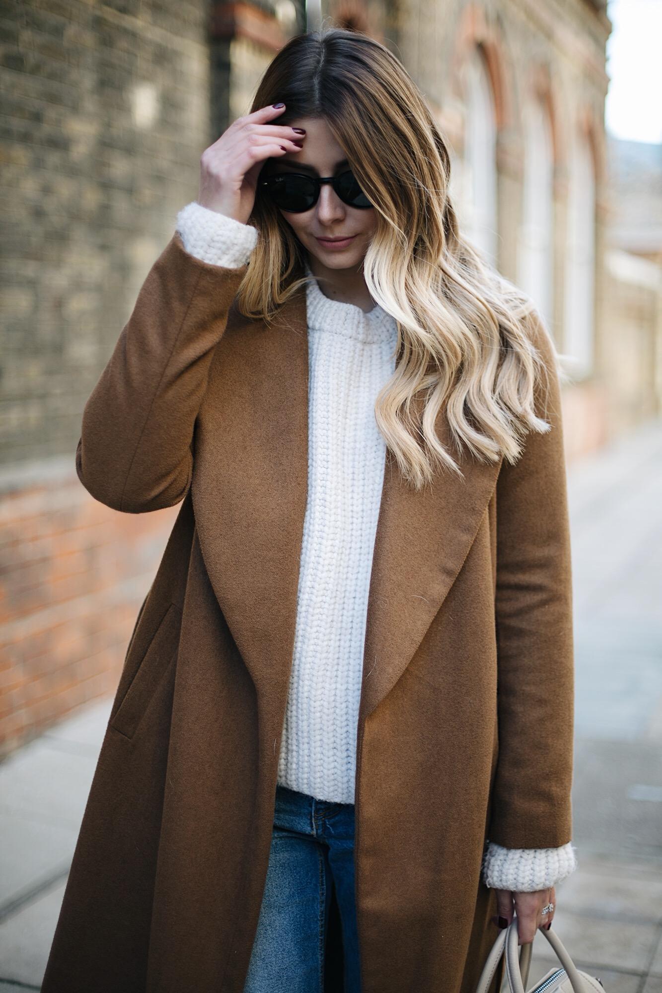 Tan coat, cream sweater, long balayage hair