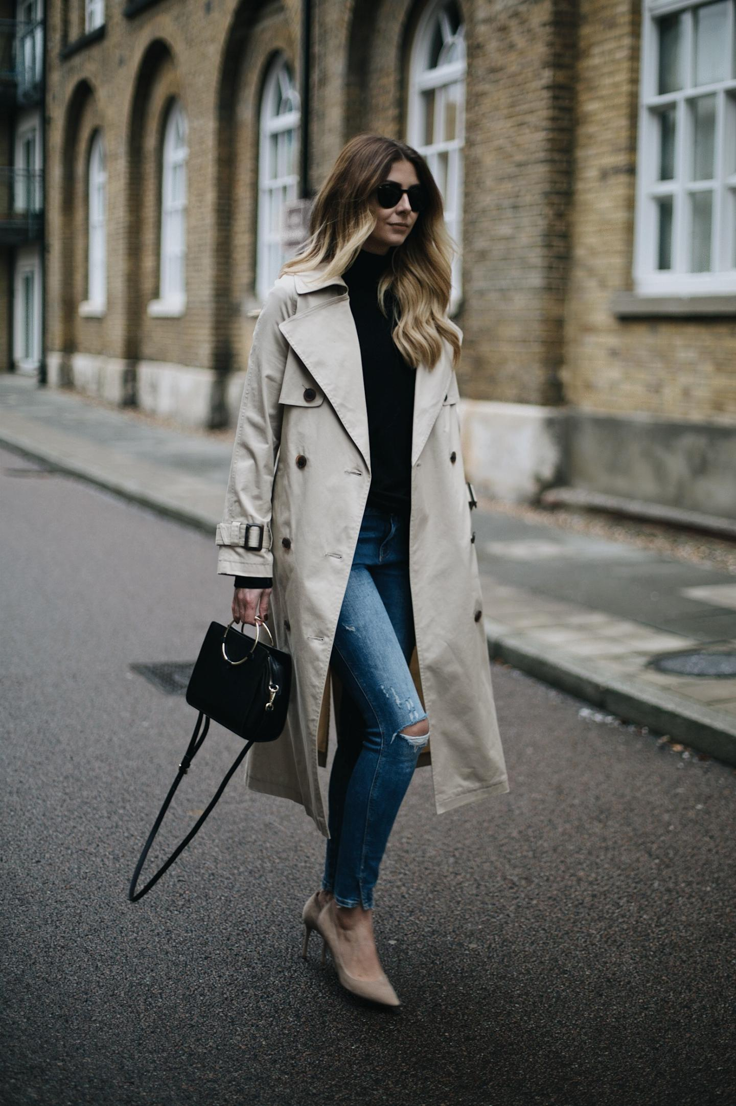 maxi trench coat, ripped skinny jeans, black polo neck jumper, ring handle bag, suede pumps