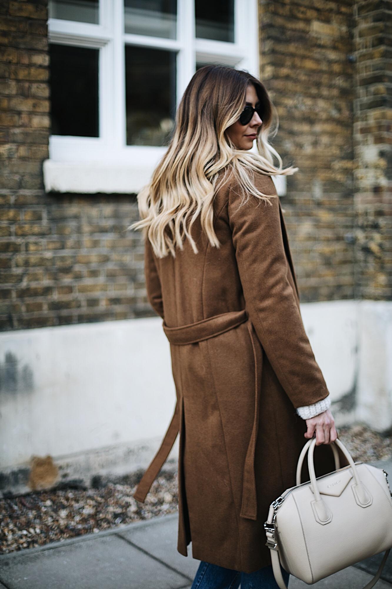 Tan belted coat, long blonde balayage hair