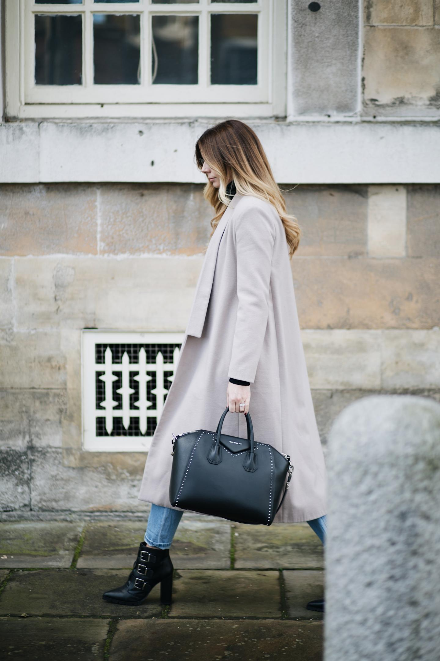 Emma Hill wears nude coat, studded medium Givenchy Antigona bag, bleach wash boyfriend jeans, black buckle ankle boots, winter style, winter outfit ideas