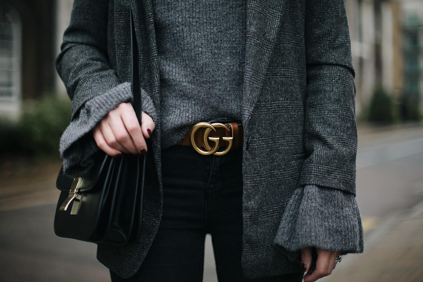 Tan leather Gucci GG belt, Celine box bag, grey bell sleeve jumper, grey check blazer, black skinny jeans