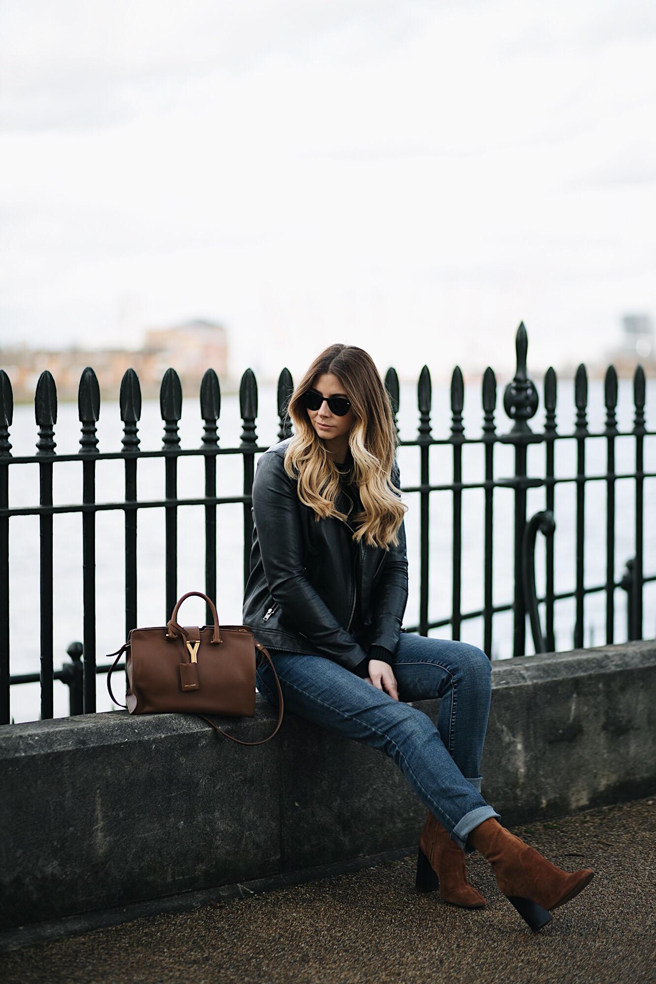 black leather biker jacket, black sweater, dark wash boyfriend jeans, tan suede ankle sock boots, tan YSL Saint Laurent Chic Cabas, winter outfit