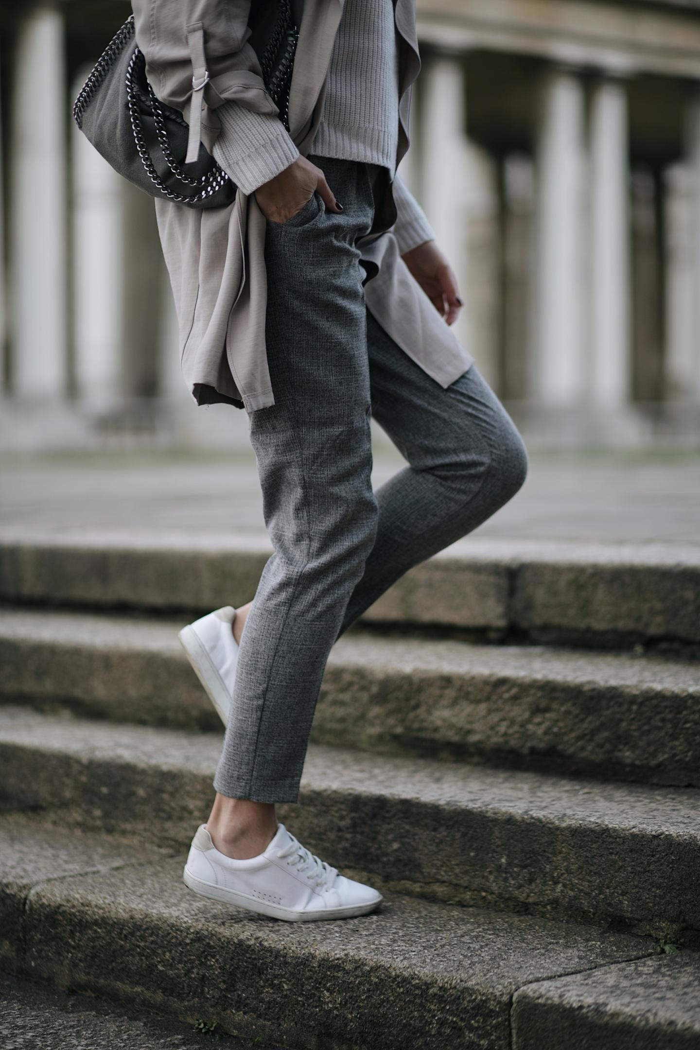 grey tailored trousers, beige jacket, lace up white trainers