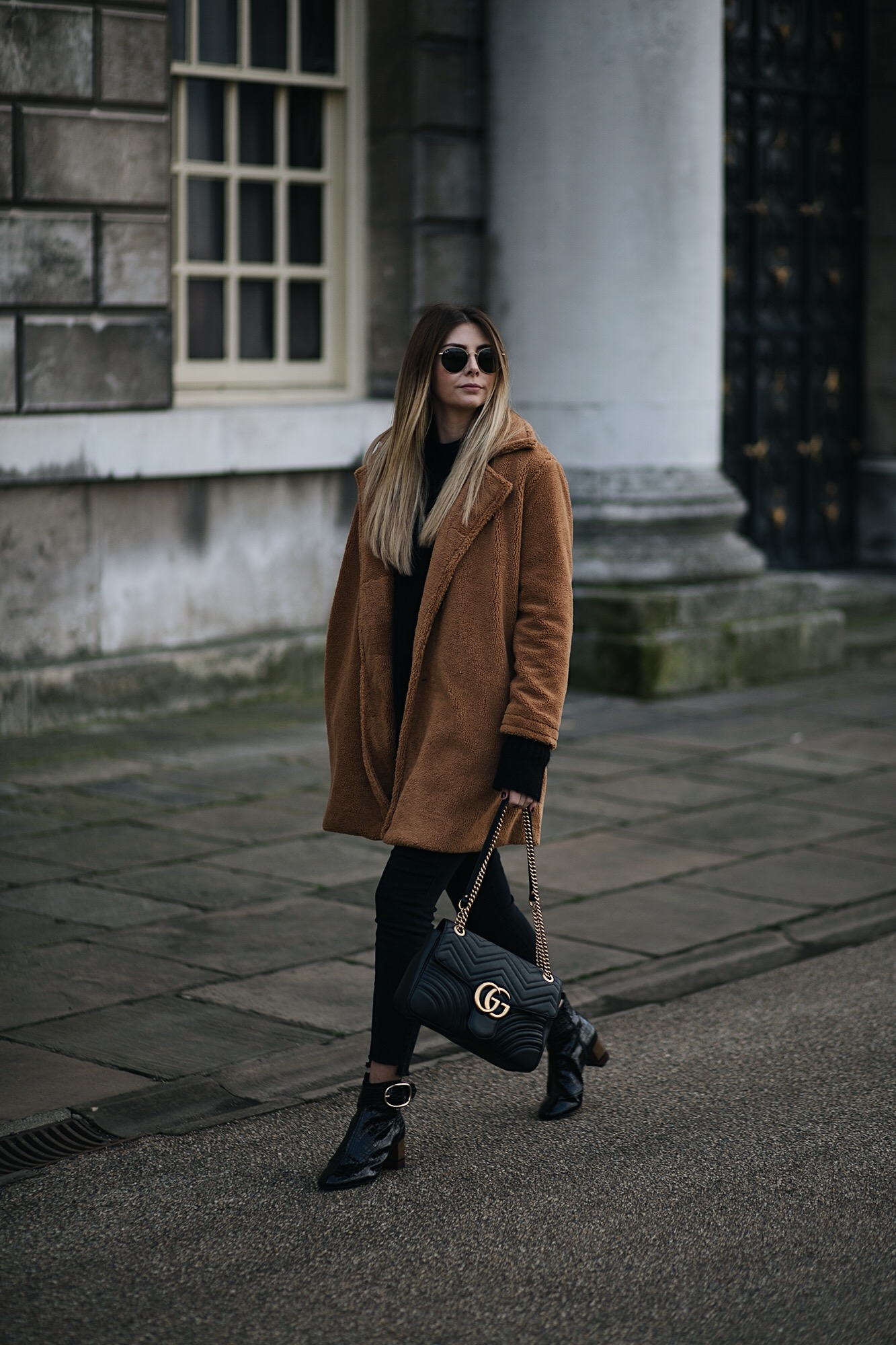Emma Hill wears camel brown teddy bear coat, Gucci medium black leather Marmont bag, black skinny frayed hem jeans, black patent ankle boots, winter outfit