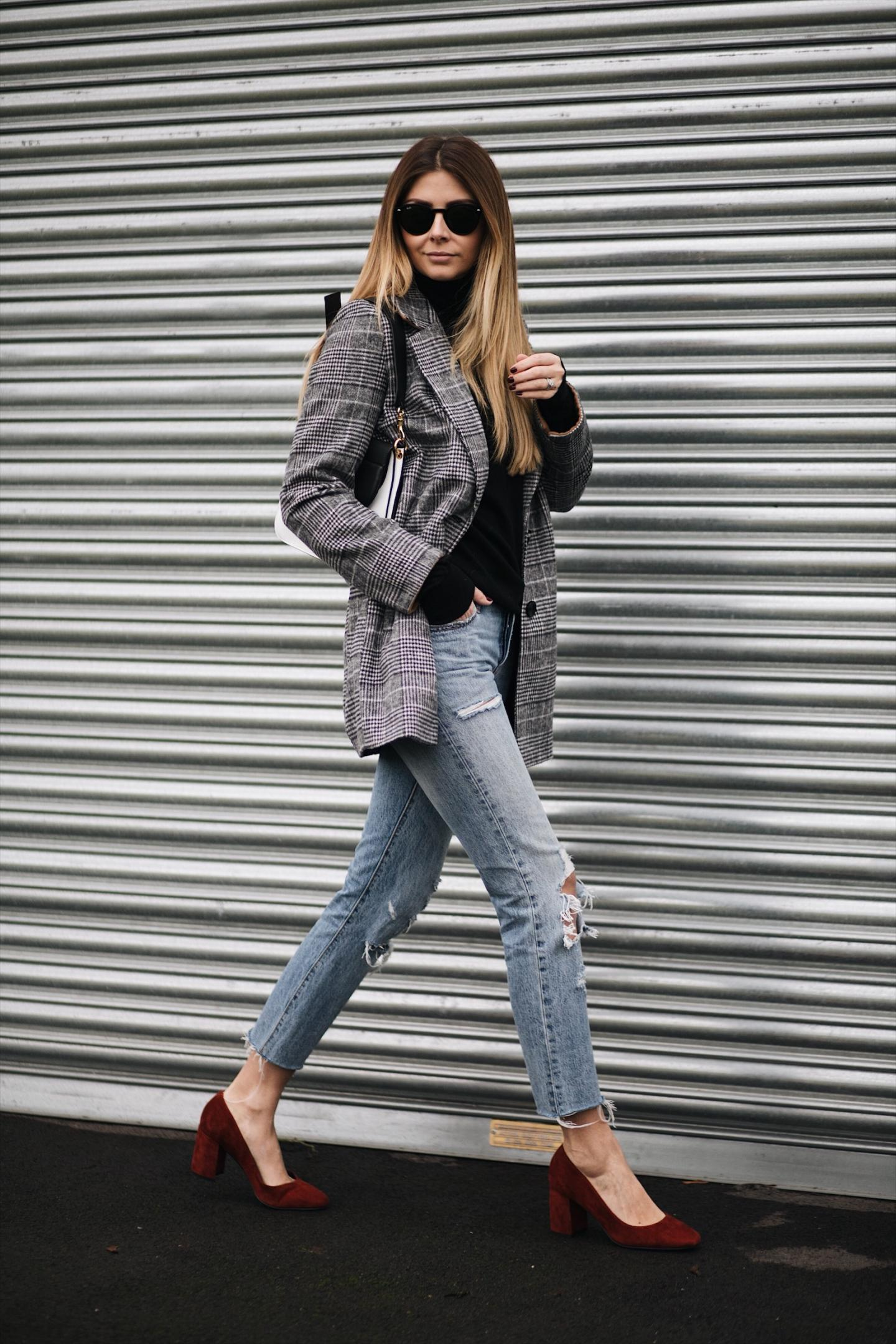 Emma Hill wears check blazer, black sweater, ripped Levis 501 jeans with raw hem, ruse suede block heel shoes, black white JW Anderson Pierce bag, winter outfit
