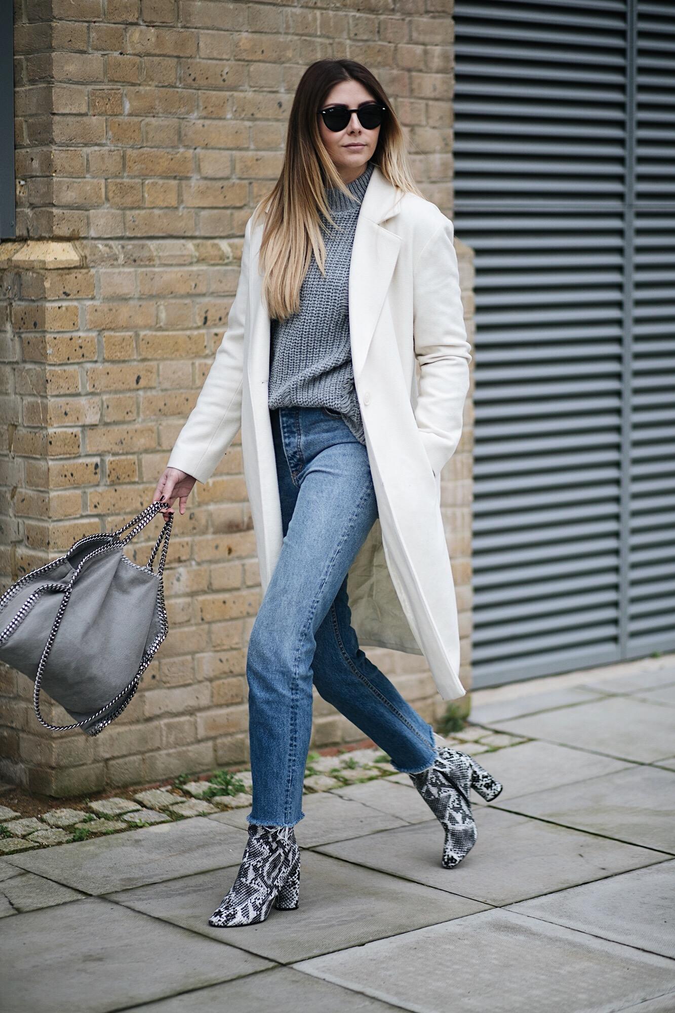 white coat, grey chunky jumper, straight leg raw frayed hem jeans, grey Stella McCartney Falabella, snakeskin boots, winter outfit