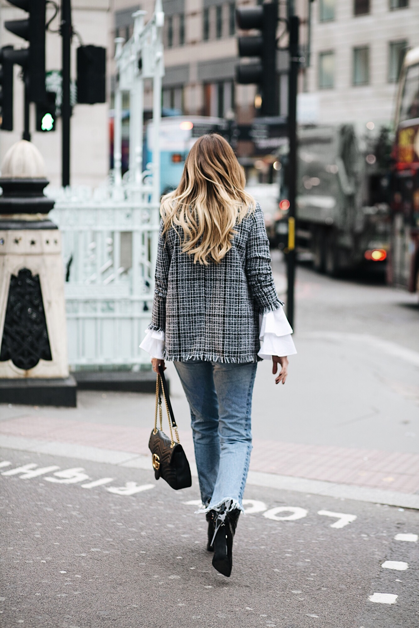Emma Hill (EJStyle) wears boucle tweed blazer, flare ruffle cuff white shirt, light wash denim stepped hem frayed jeans, Gucci Marmont bag, black pic vinyl ankle boots, London street style