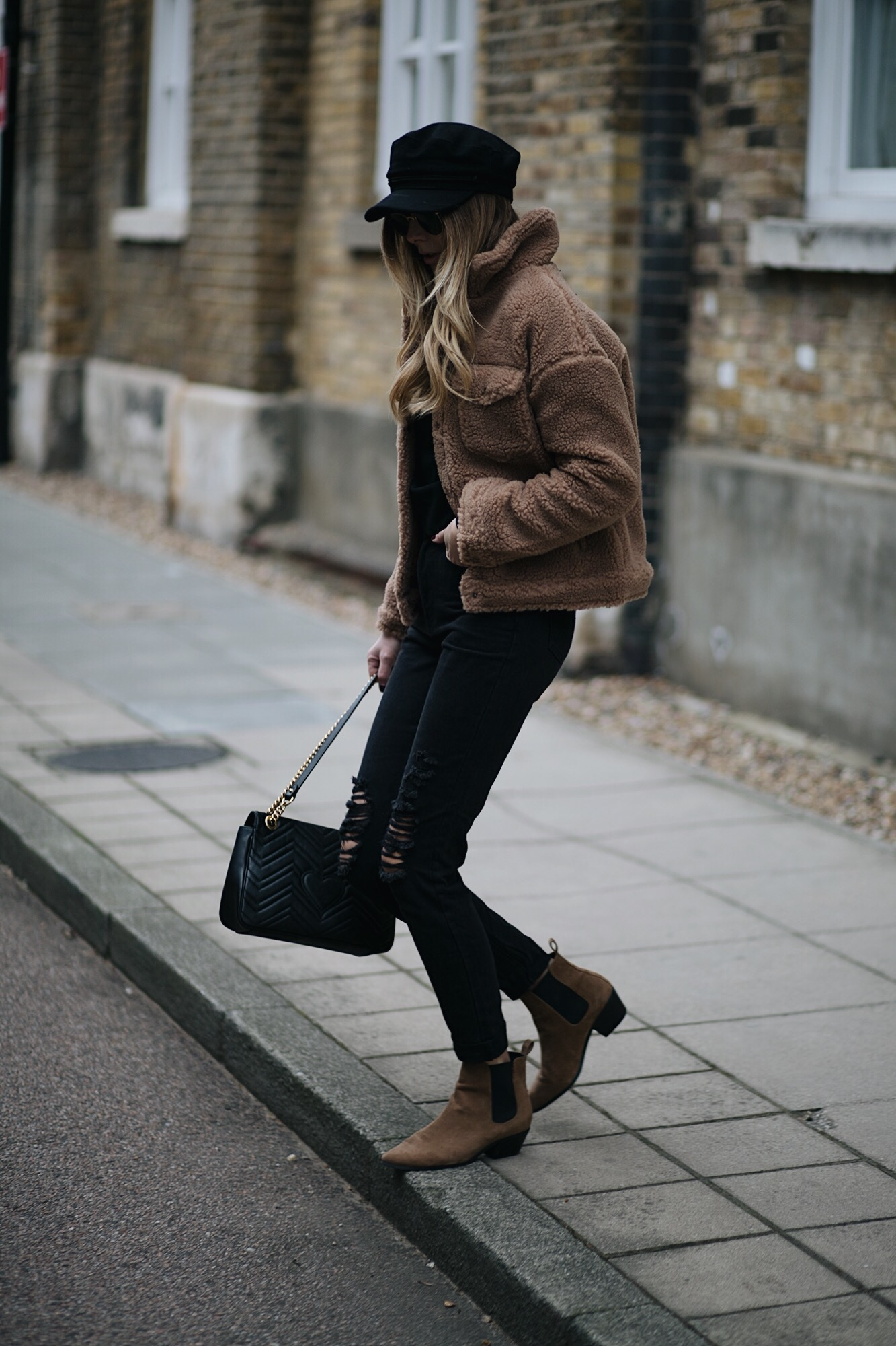 Emma Hill wear camel teddy jacket, ripped black jeans, Gucci Marmont bag, Rayban round gold sunglasses, tan suede Chelsea ankle boots, black baker boy cap hat. Casual Winter outfit