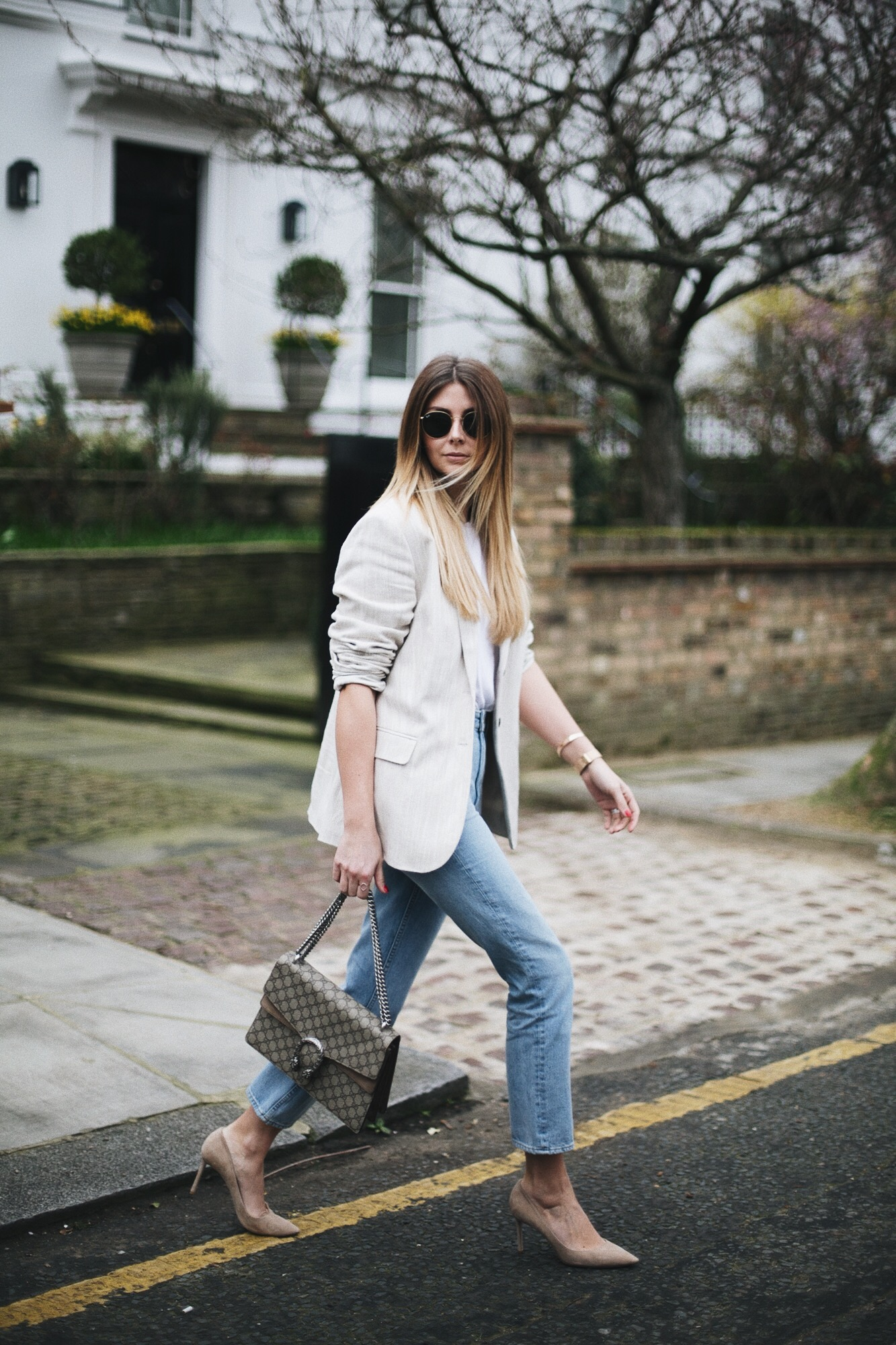 Emma Hill of EJStyle wears beige linen blazer, light wash high waisted jeans, Gucci medium beige Dionysus bag, small arm tattoo, rose gold accessories, beige suede Jimmy Choo pumps, spring outfit