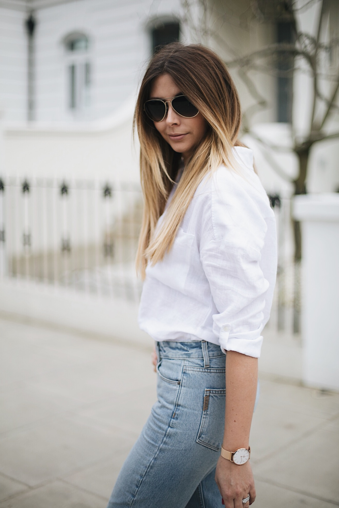 white shirt, gold disc necklace, gold aviator sunglasses, light wash denim
