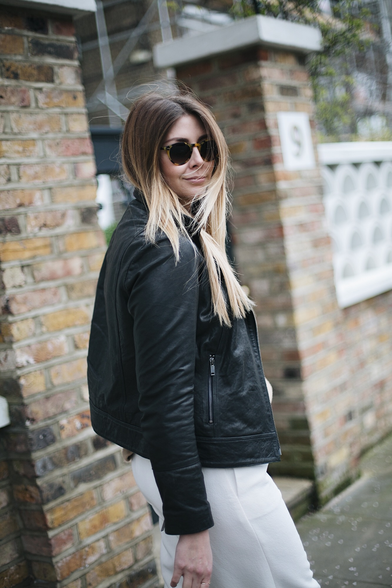 black biker leather jacket, round sunglasses, white wide leg trousers