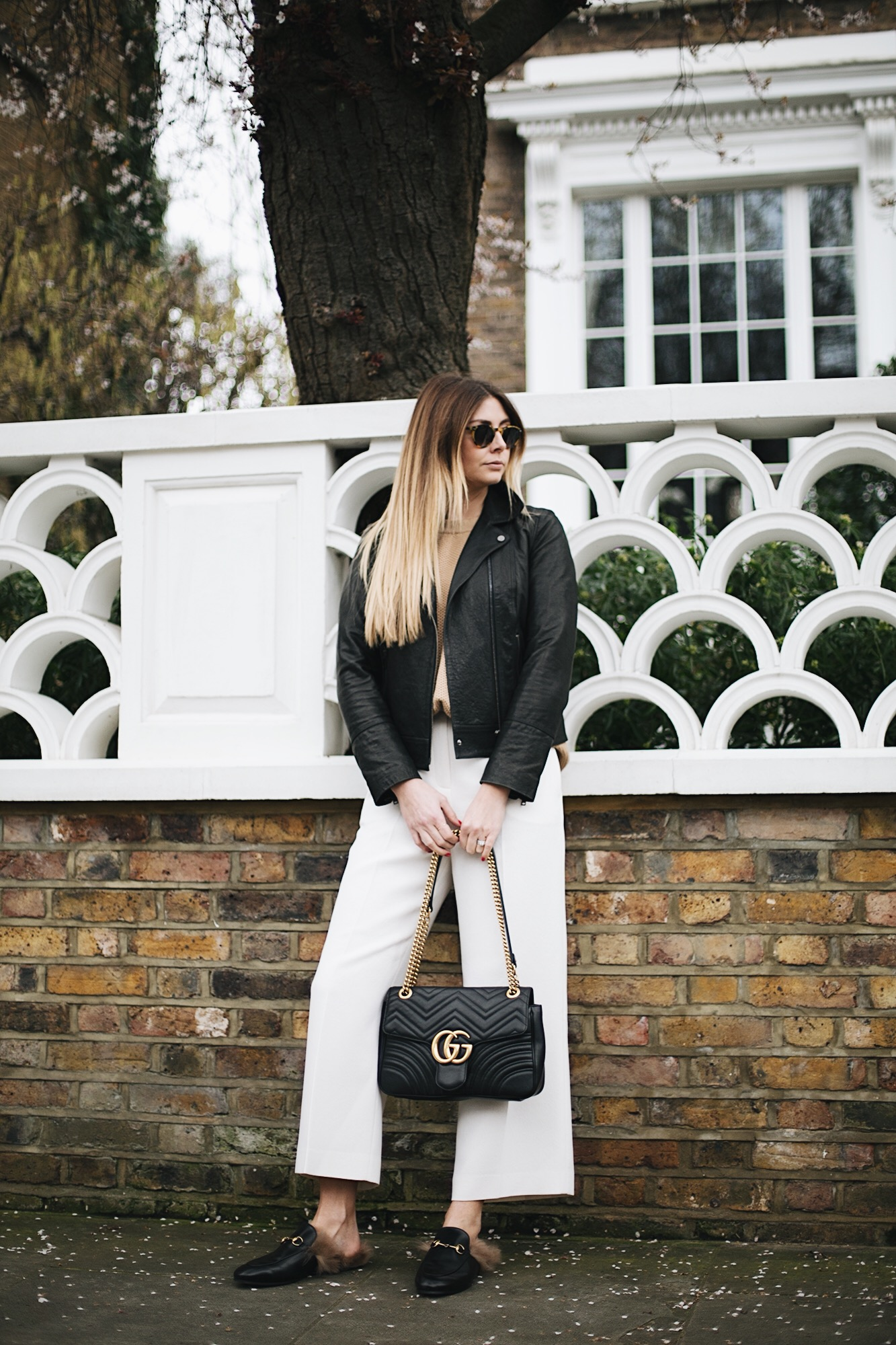 black biker leather jacket, round sunglasses, white wide leg trousers, Gucci Princetown slippers, Gucci Marmont bag