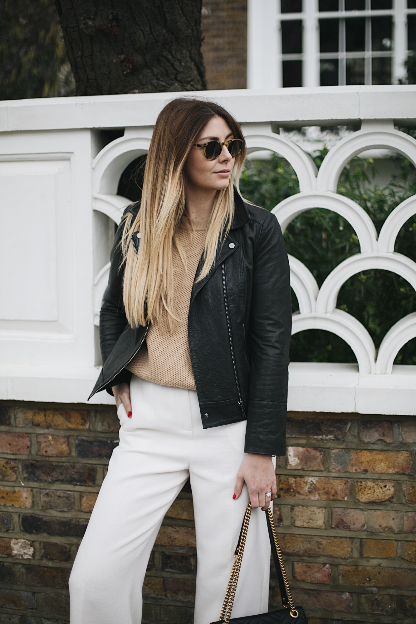 biker jacket, camel knit, white wide leg cropped trousers, round sunglasses