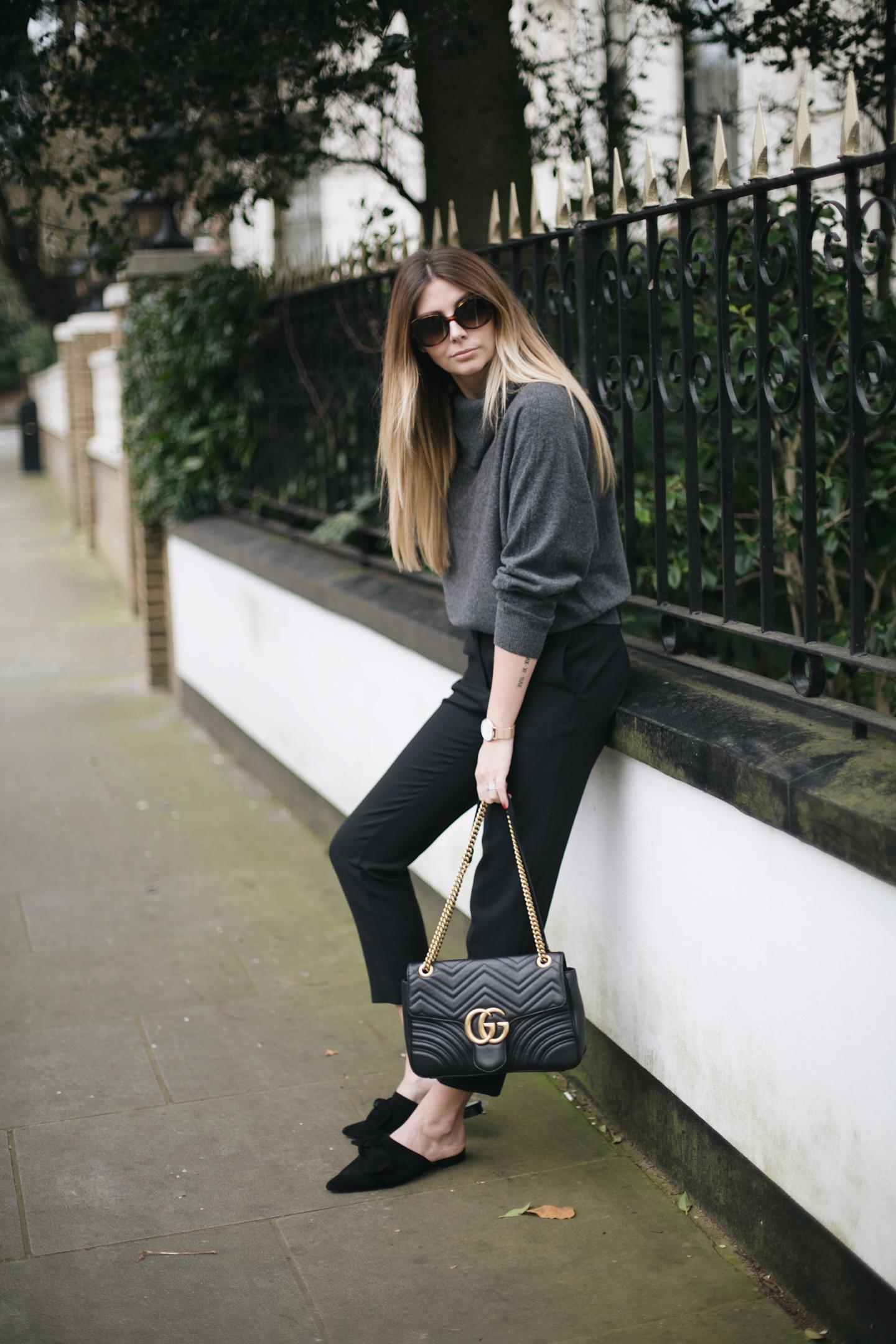 grey cashmere cowl neck sweater, black tailored trousers, oversized sunglasses, Gucci Marmont bag, suede bow slides