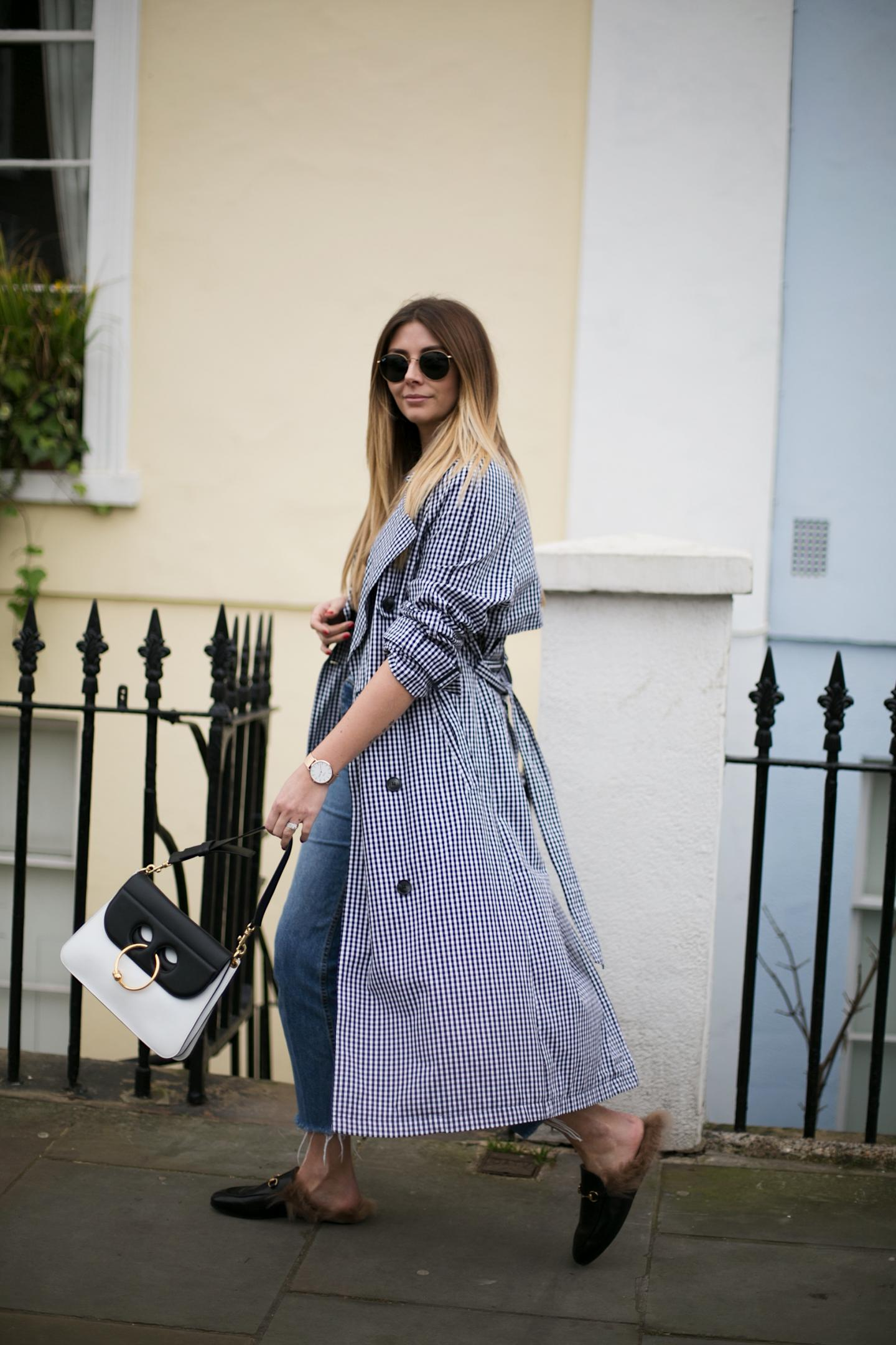 Gingham trench coat, frayed hem jeans, J.W. Anderson monochrome Pierce bag, Gucci Princetown fur slippers, Spring street style outfit